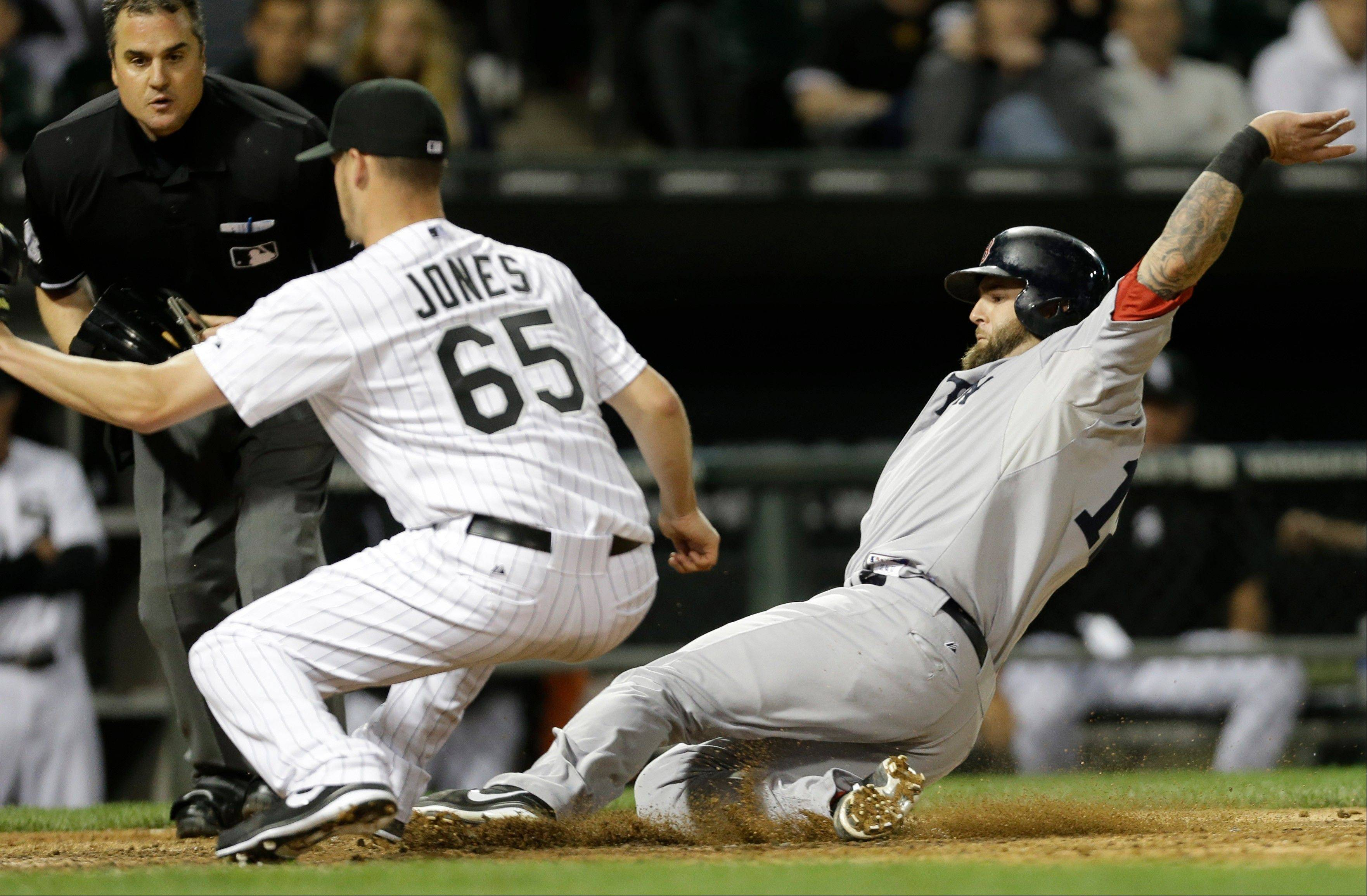 Boston Red Sox's Mike Napoli, right, scores after a passed ball as Chicago White Sox relief pitcher Nate Jones (65) waits for the ball during the eighth inning of a baseball game in Chicago, Wednesday, May 22, 2013. (AP Photo/Nam Y. Huh)