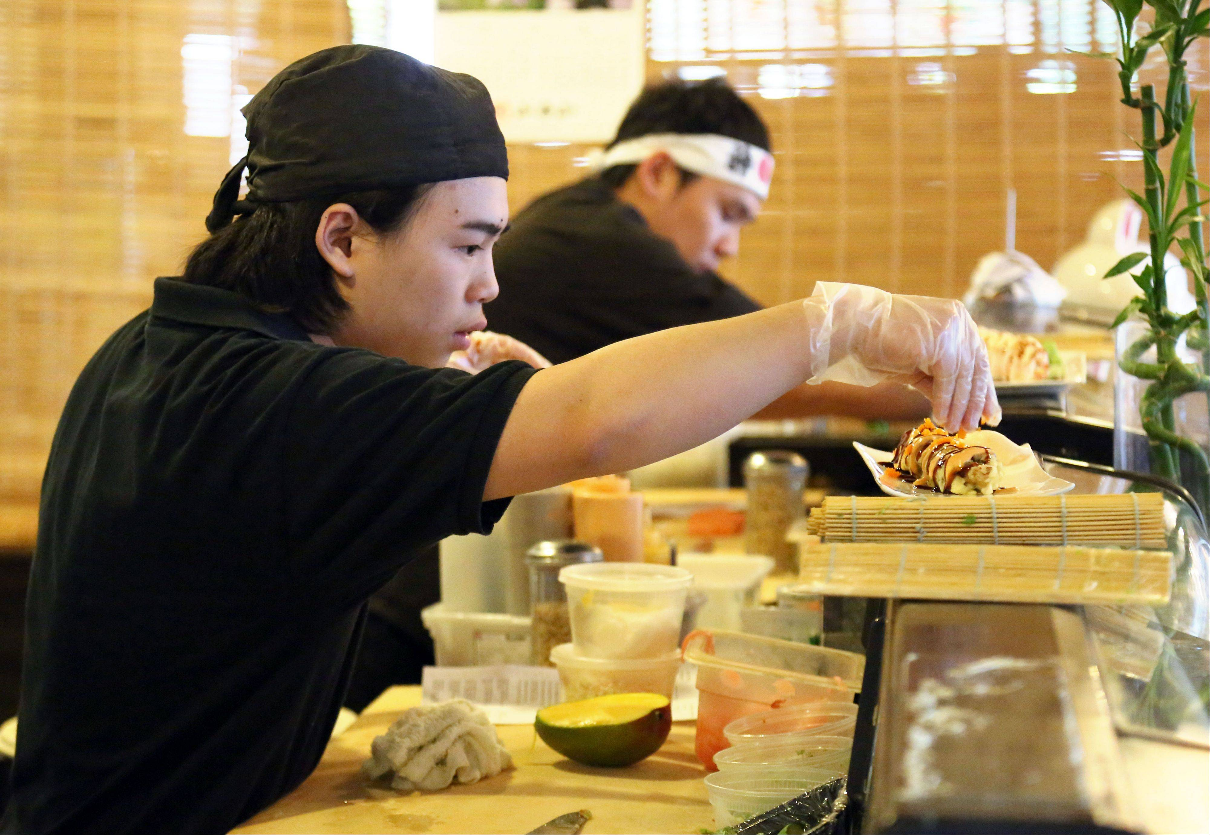 Sushi chefs Andy Au, left, and Jimmy Li create satisfying rolls at Kawa Japanese Restaurant and Mongolian Grill in Grayslake.