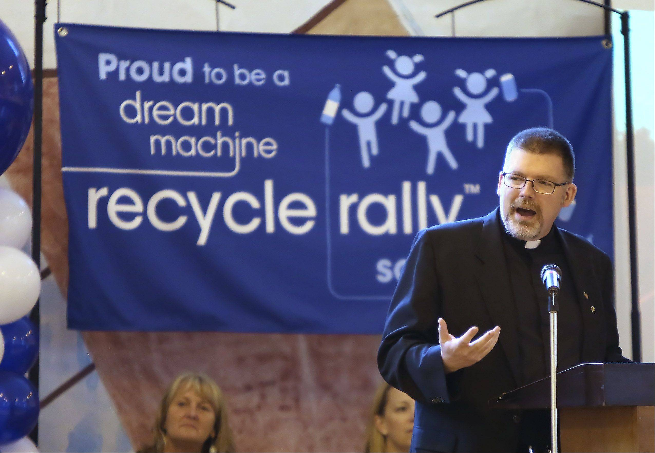 St. Bede Catholic Parish's Rev. Tim Fairman congratulates students at the Ingleside school on winning a $25,000 grand prize from PepsiCo's Dream Machine Recycle Rally.