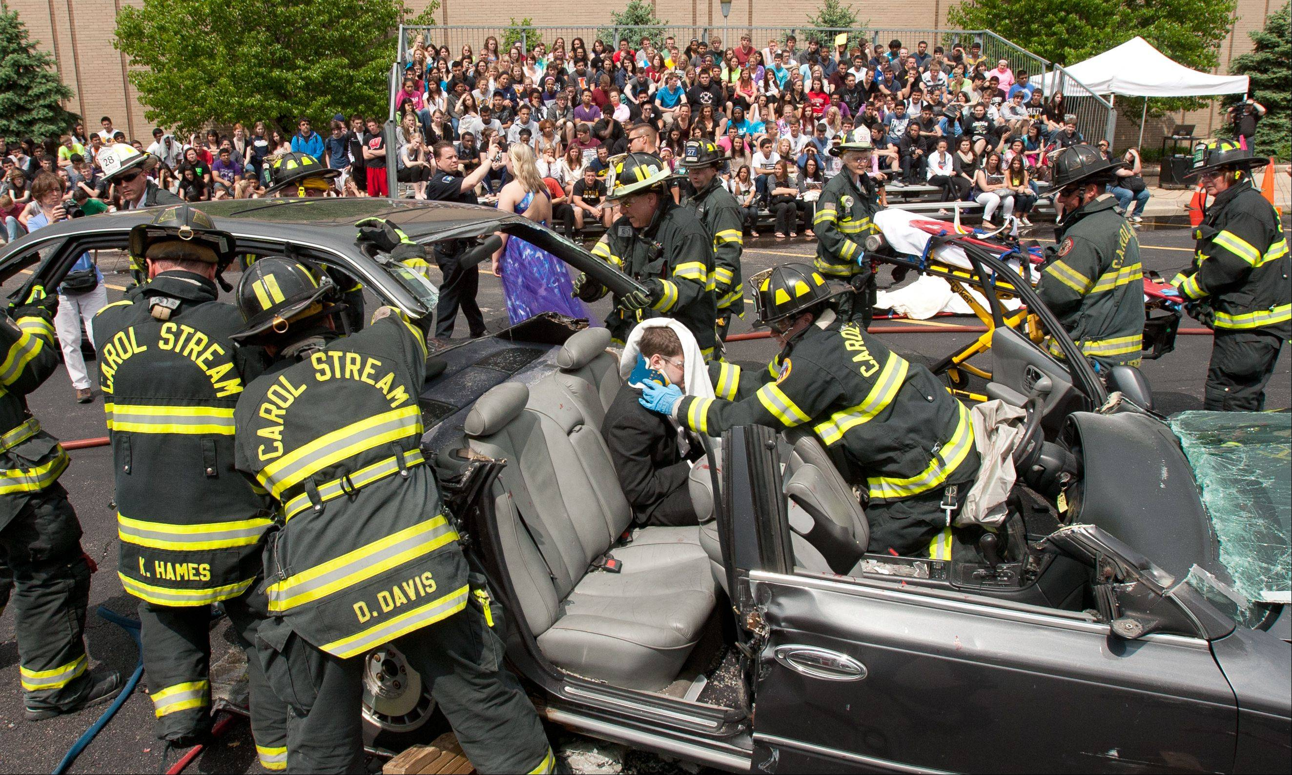 Carol Stream firefighters remove the roof of a car Wednesday during a mock DUI fatal car crash demonstration to extricate a student actor playing a victim.