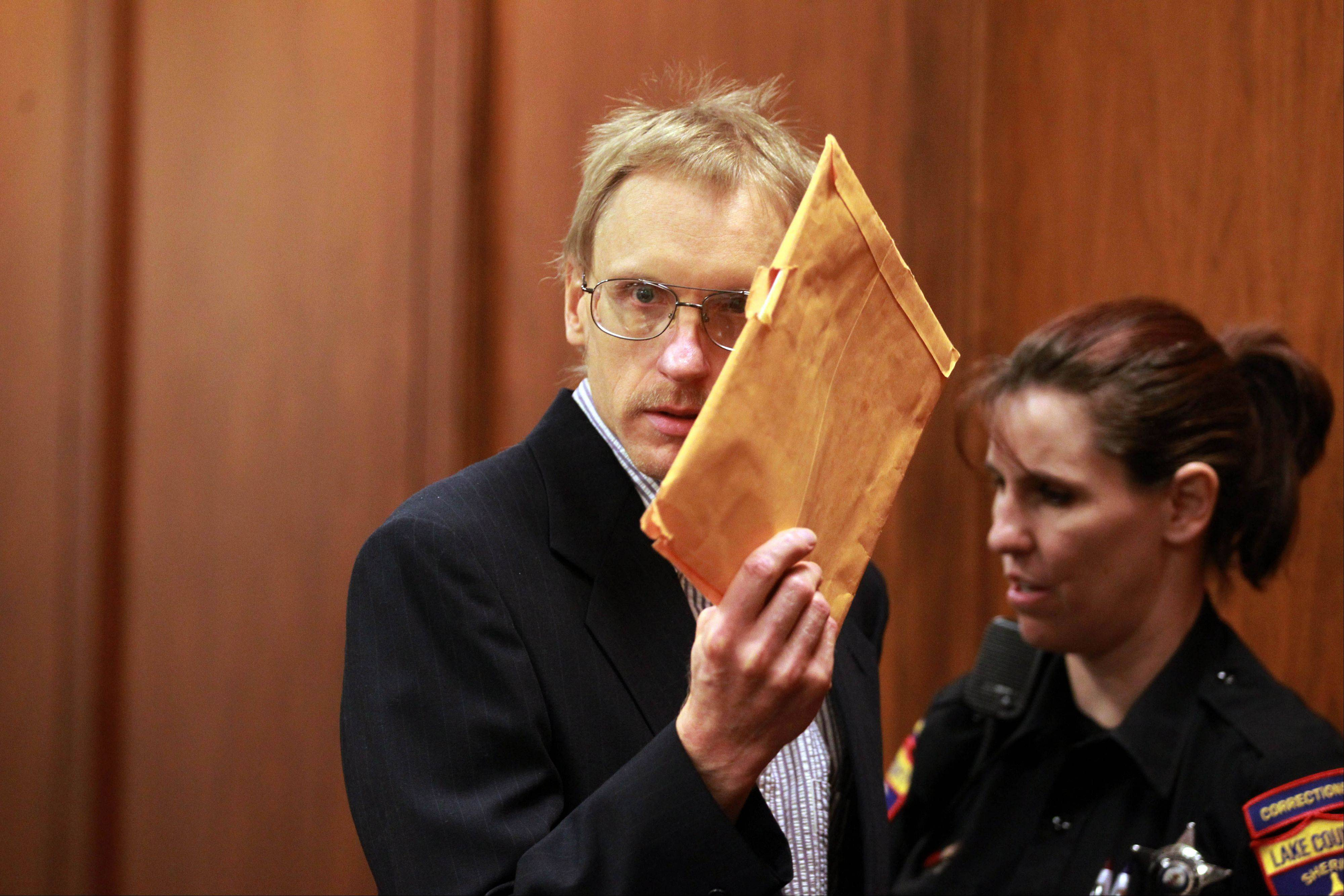 Ronald Stolberg covers his face as he enters the courtroom of Judge Mark Levitt in Lake County on Wednesday. Stolberg is on trial for the 2011 first-degree murder for his wife, Rachel Stolberg.