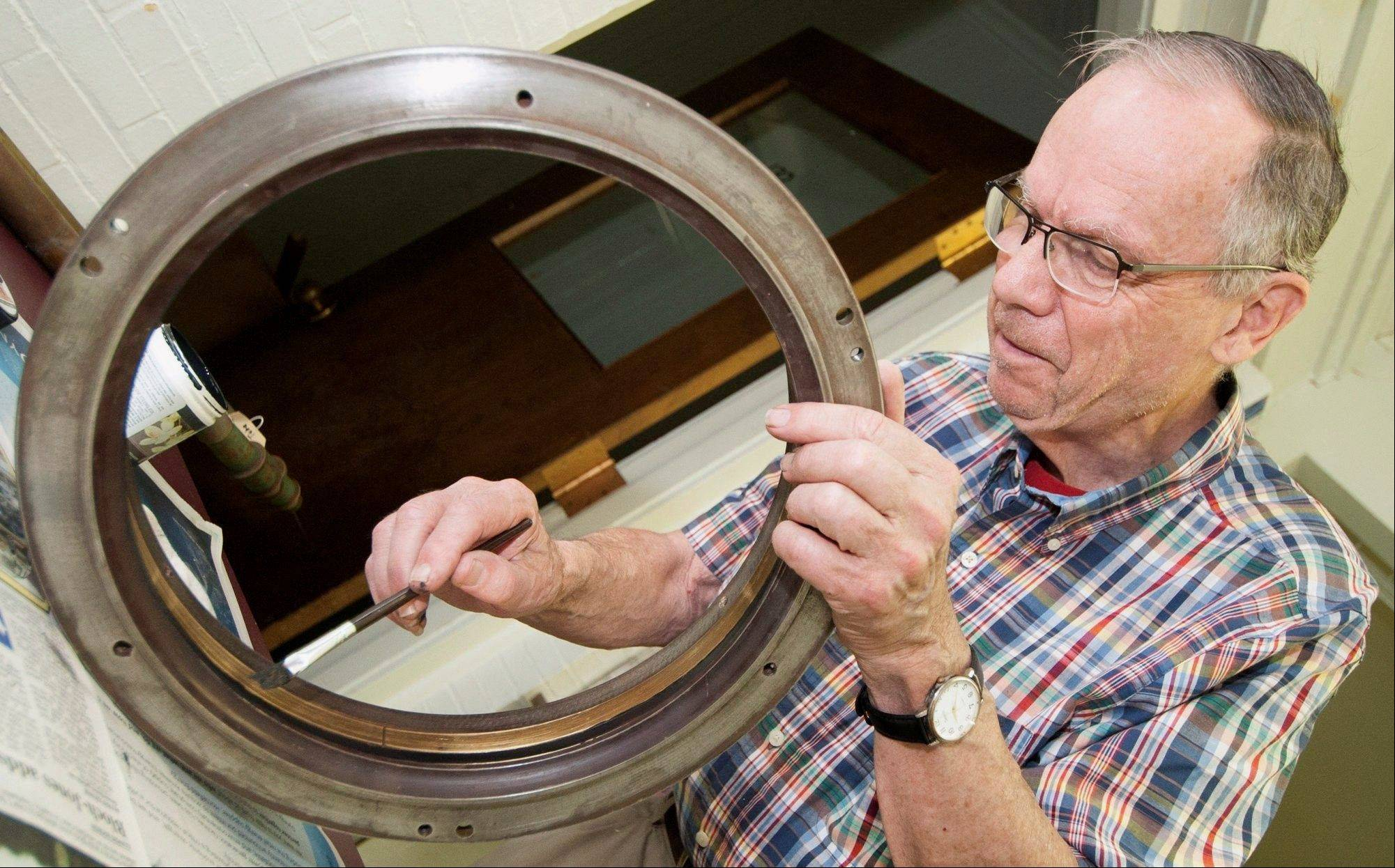 Chris Ray, owner of Ray Museum Studios in Swarthmore, Pa., paints the inside of the lens so it will not reflect light as crews take apart the historic 117-year-old telescope at the University of Illinois observatory in Urbana.