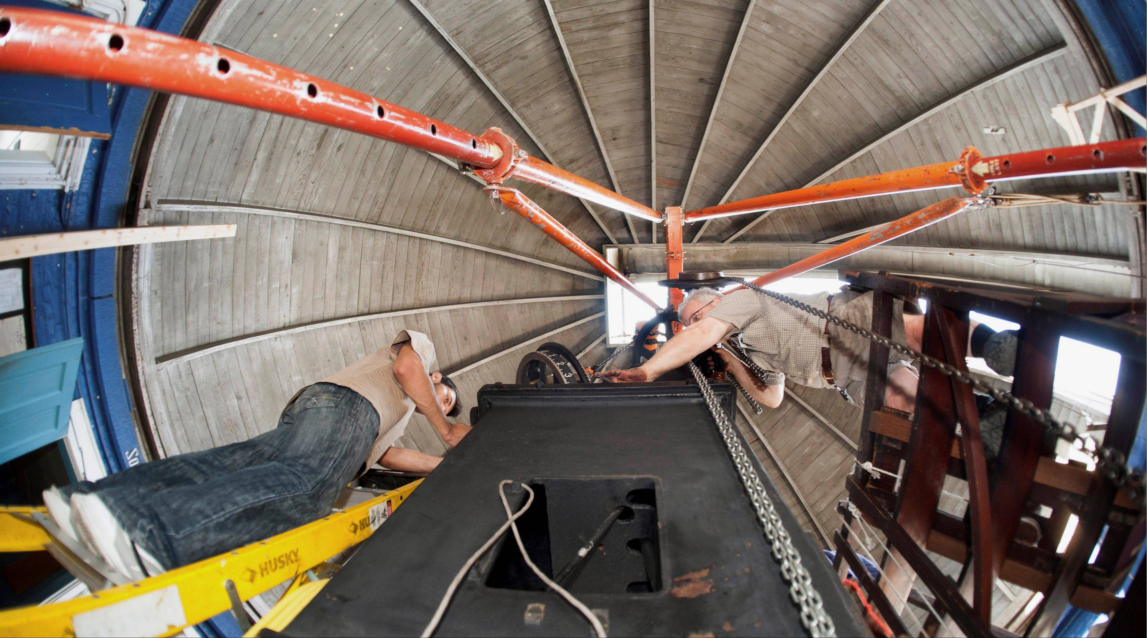 Swarthmore engineering sophomore Yousef Alhessi, left, and Fred Orthlieb, emeritus professor of mechanical engineering at Swarthmore, work on taking apart the historic 117-year-old telescope at University of Illinois observatory.