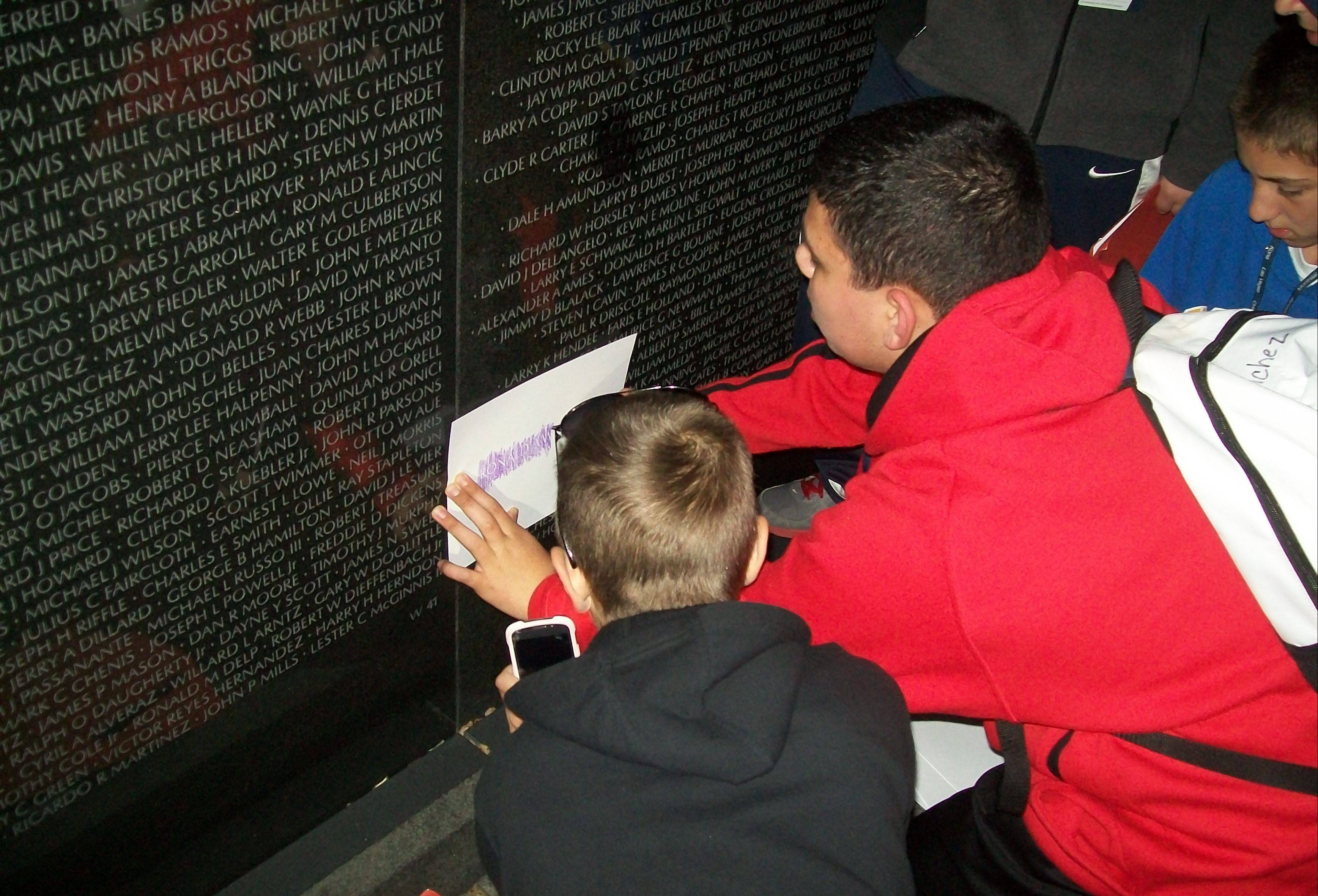 Christian Sanchez, 13, of Carpentersville, in the red jacket, rubs a print over his great uncle, Army First Lt. Ronald Wolter's name during a school trip last week to the Vietnam Veterans Memorial Wall. Wolter, of Carpentersville, was killed in combat in 1968 and has a band shell named after him in his hometown.