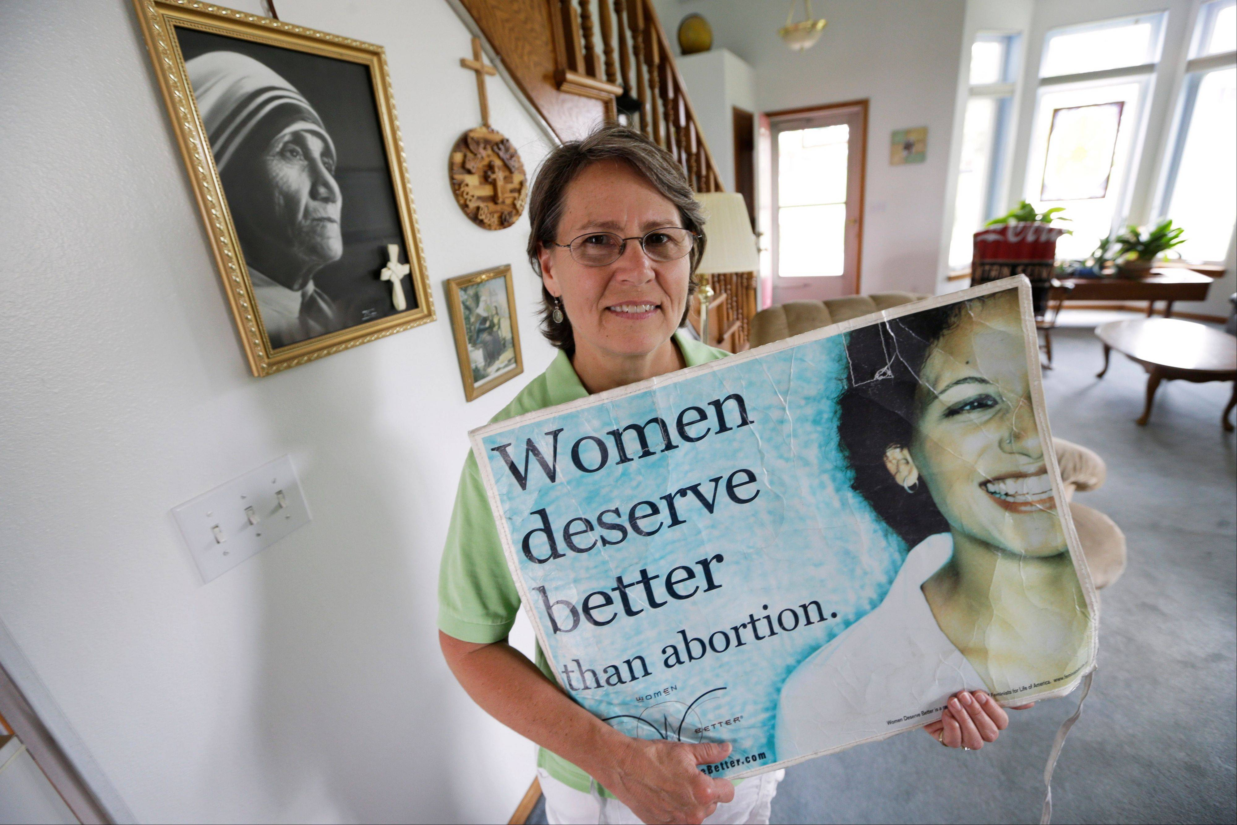 Coalition for Life of Iowa president Sue Martinek holds a sign in her home, Tuesday