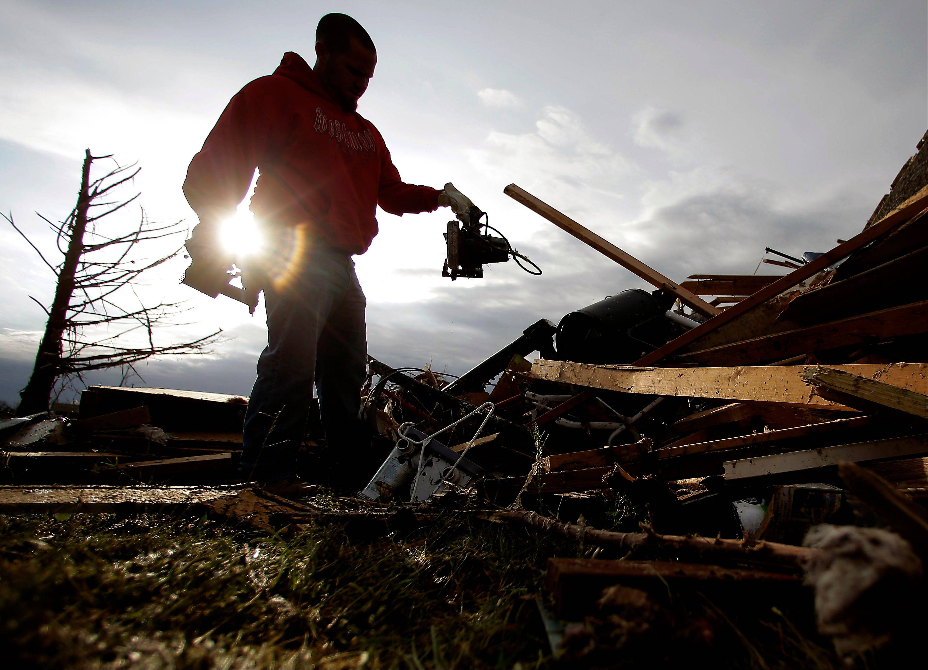Zac Woodcock salvages items from the rubble of a tornado-ravaged rental home which he owns Tuesday in Moore, Okla.