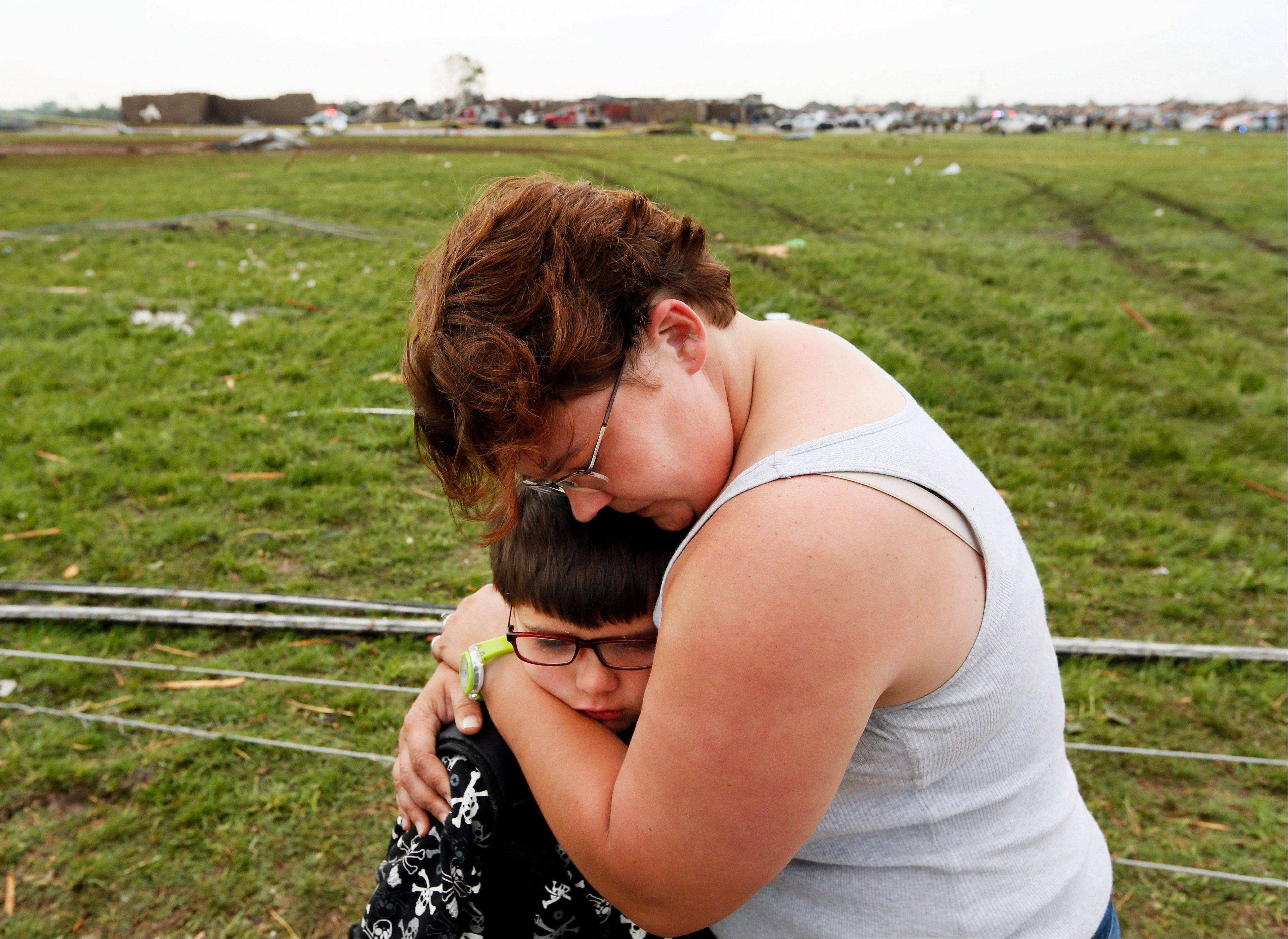 Rebekah Stuck hugs her son, Aiden Stuck, 7, after she found him in front of the destroyed Briarwood Elementary after a tornado struck south Oklahoma City and Moore, Okla., Monday, May 20, 2013. Aiden Stuck was inside the school when it was hit.