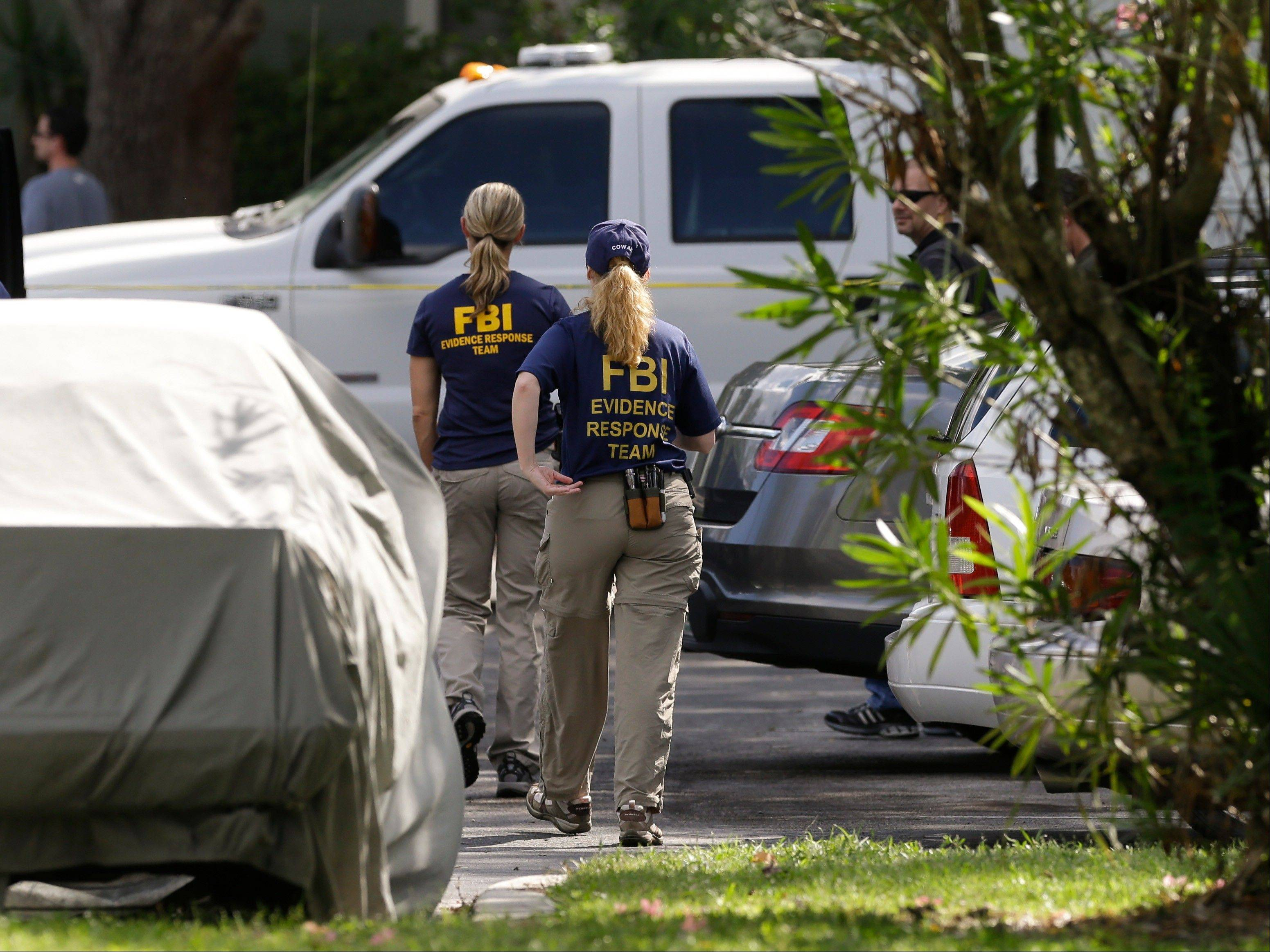 FBI investigators walk near the crime scene of an apartment where a man was shot by an FBI agent Wednesday in Orlando, Fla. The man who was shot and killed by the agent early this morning was friends with the Boston bombings suspects, according to a friend of the victim.