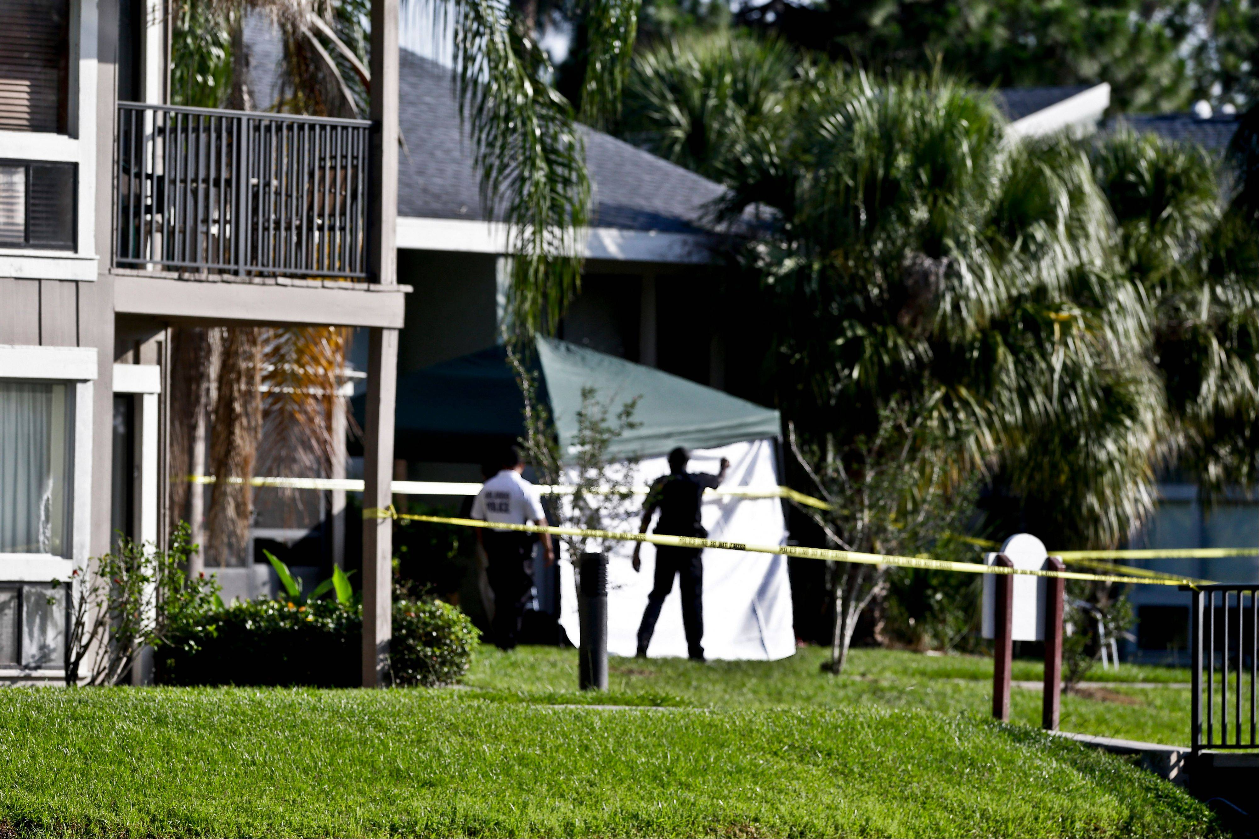 Investigators stand outside an apartment complex where a man was fatally shot when a team of FBI agents swarmed his home early Wednesday in Orlando, Fla. The FBI says the man, being questioned by authorities in the Boston bombing probe, was fatally shot when he initiated a violent confrontation, authorities said.