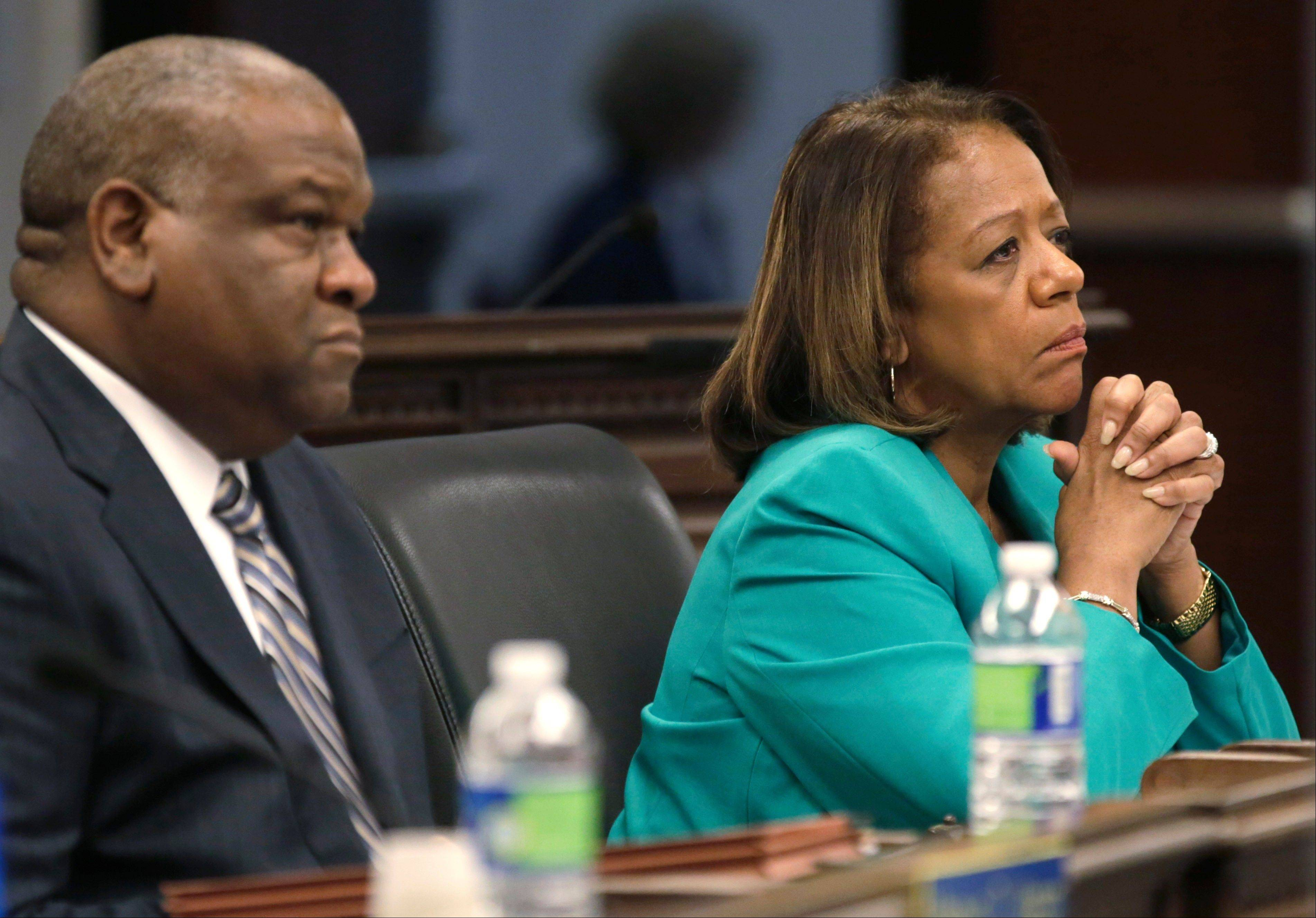 Chicago Board of Education General Counsel James Bebley and CEO Barbara Byrd-Bennett listen as Chicago Teachers Union President Karen Lewis speaks at a packed board meeting Wednesday in Chicago.