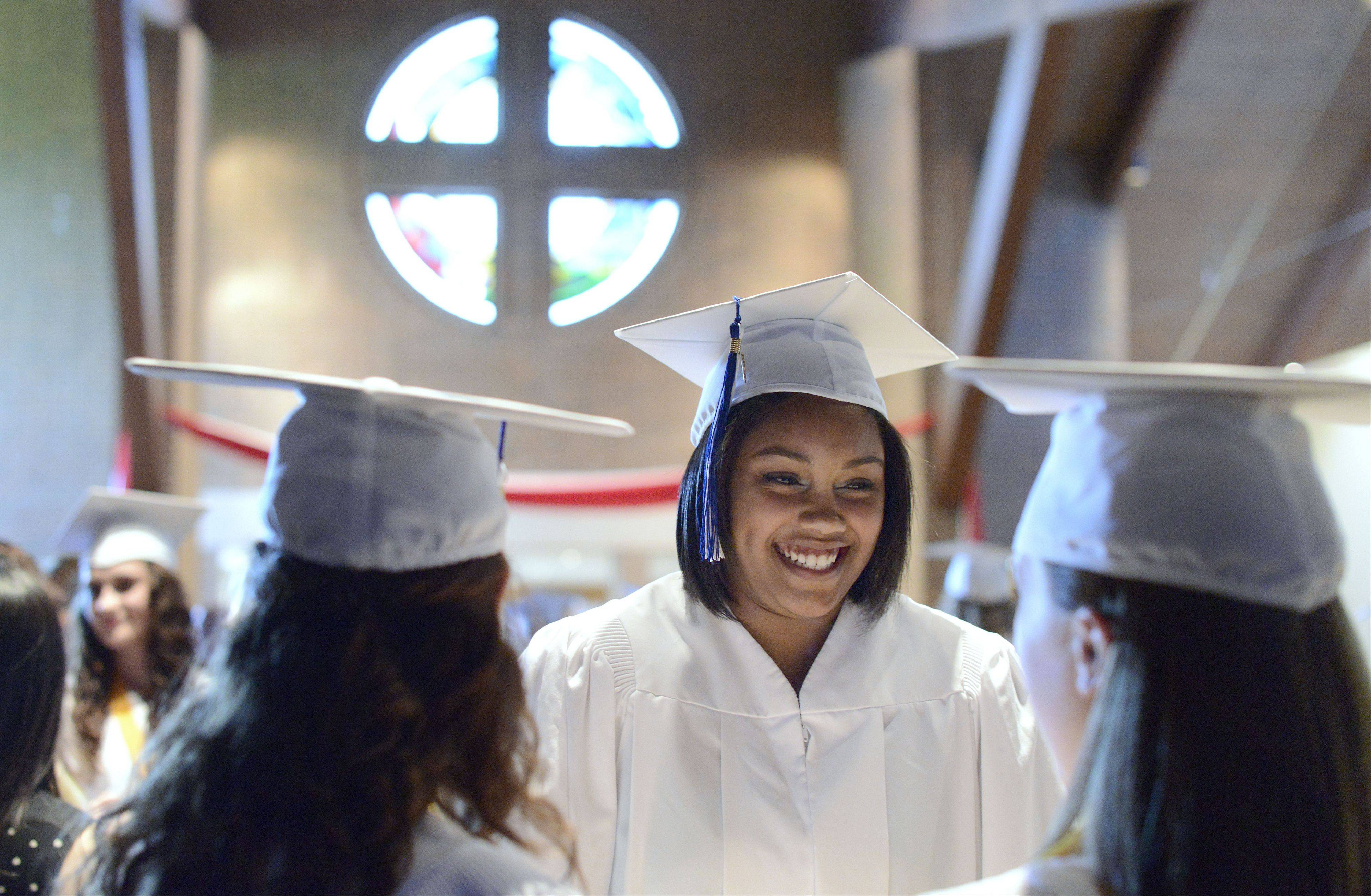 Briana Flagg, of Naperville, facing, chats with friends Kayla Emory of Aurora and Meredith Crantz of North Aurora, all 18, as their wait for the start of their graduation ceremony.
