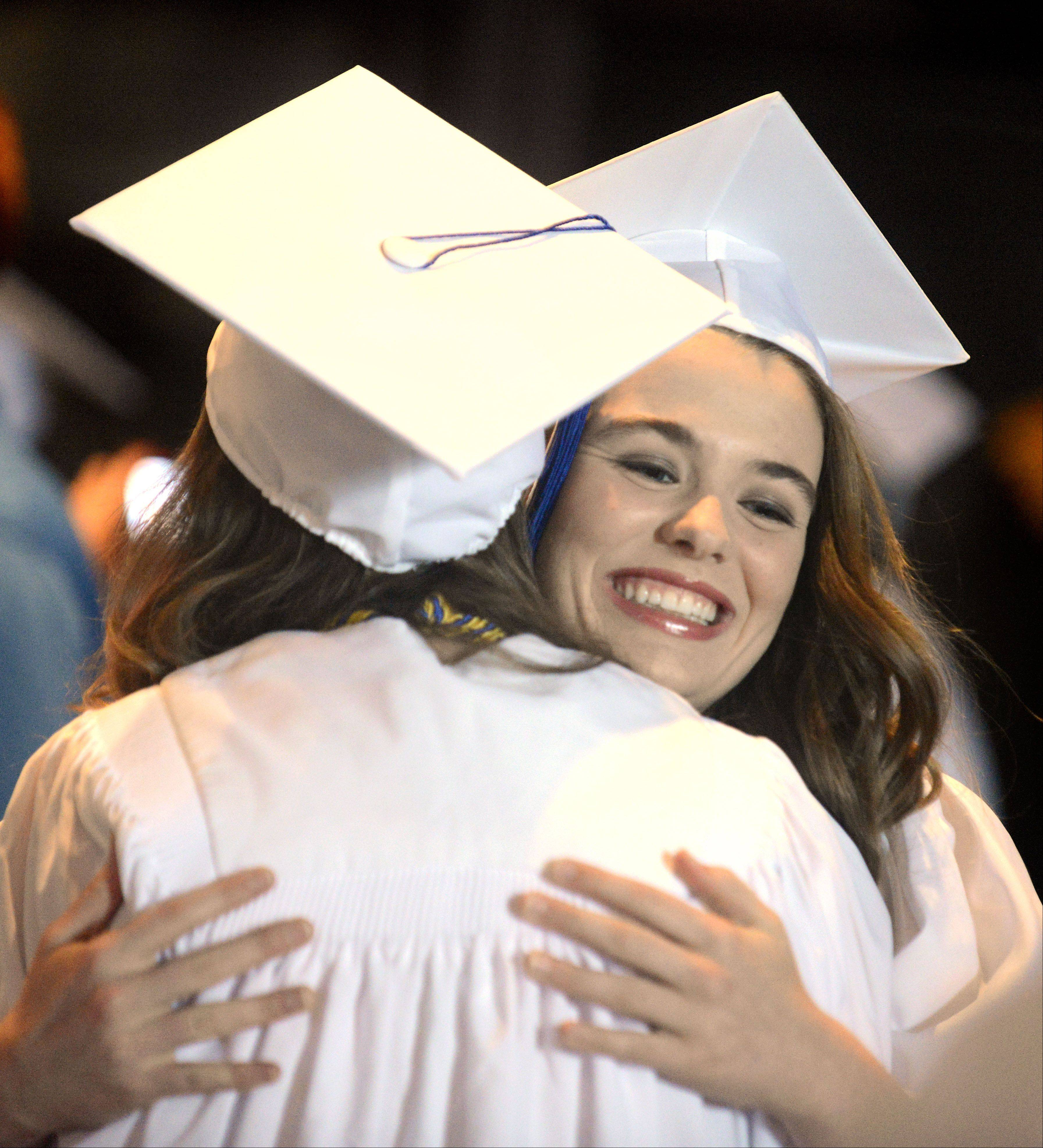 Alexandra Joyce, 18, of Aurora, facing camera, hugs fellow Rosary High School graduate Abigail Urbik, 18, of Lisle, before the start of their commencement ceremony.