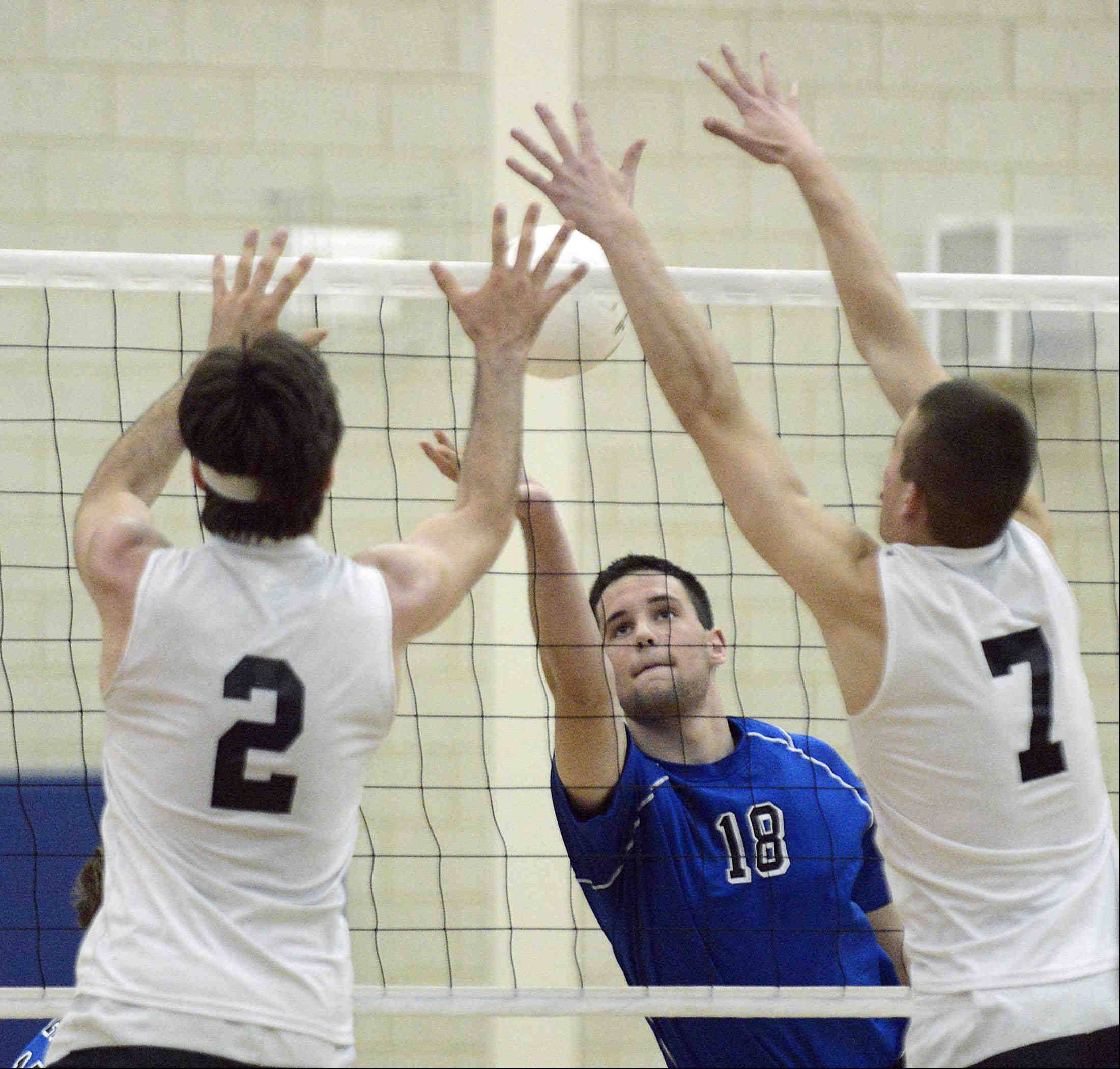Geneva's Nick Buseki tries to lift a shot over the defense of St. Charles North's Johnathan Orech and Zach Ziesmer, right, Wednesday at the Geneva regional championship match.