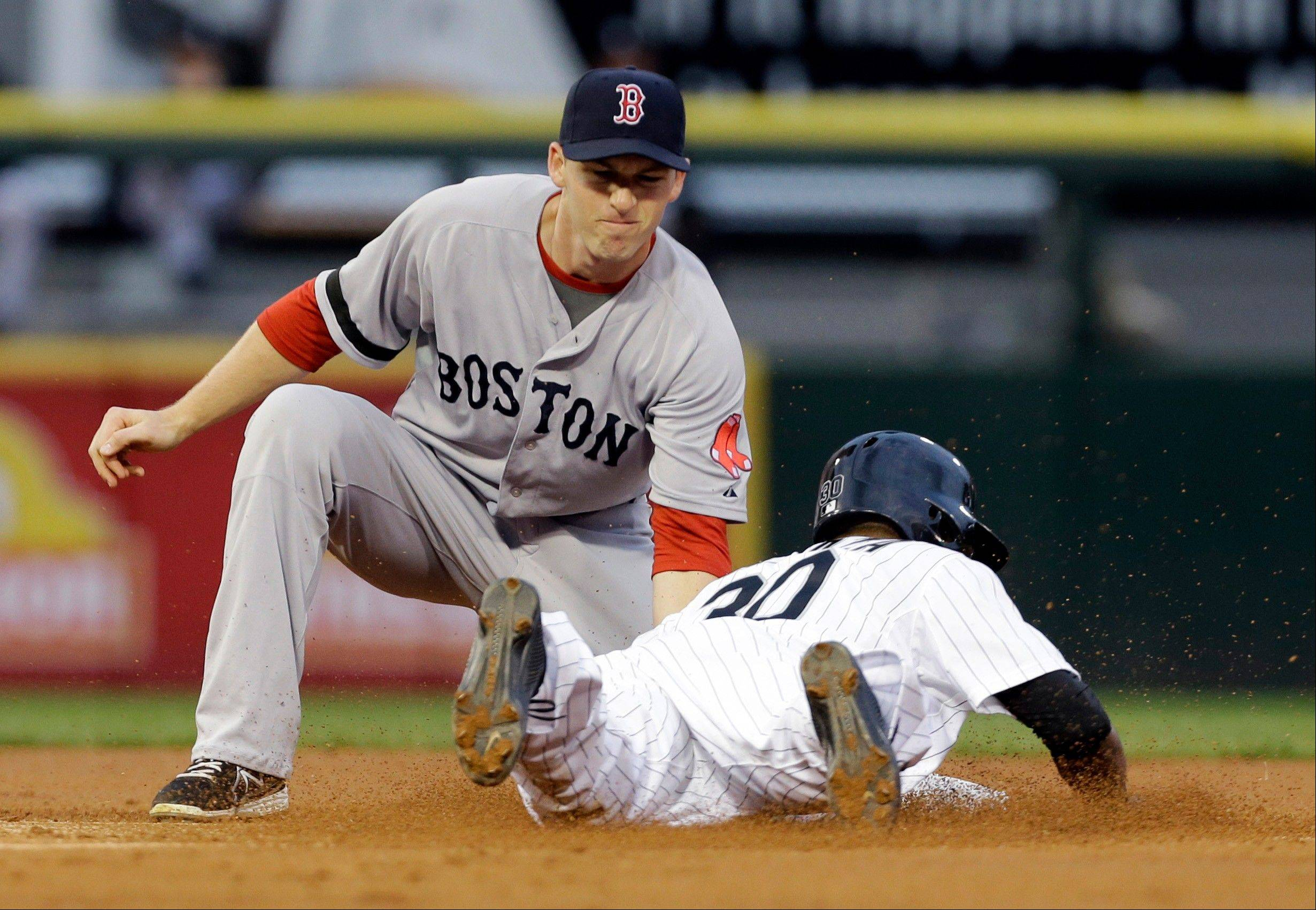 Boston Red Sox shortstop Stephen Drew, left, tags out Chicago White Sox's Alejandro De Aza during the first inning of a baseball game in Chicago, Wednesday, May 22, 2013.