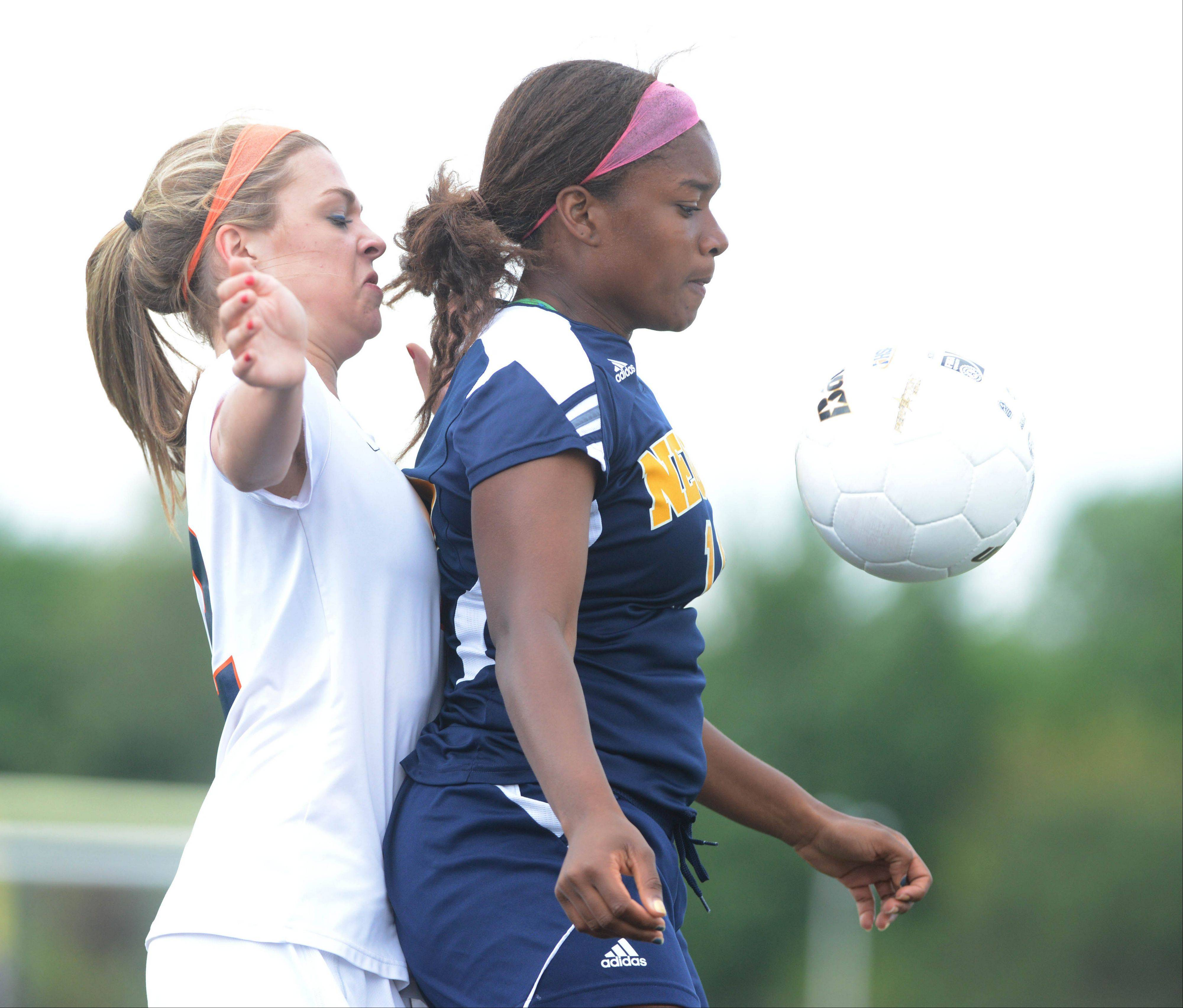 Abby Mangefrida,left, of Naperville North and Dannah Williams of Neuqua bump the ball during the Class 4A Bolingbrook girls soccer semifinals Wednesday.