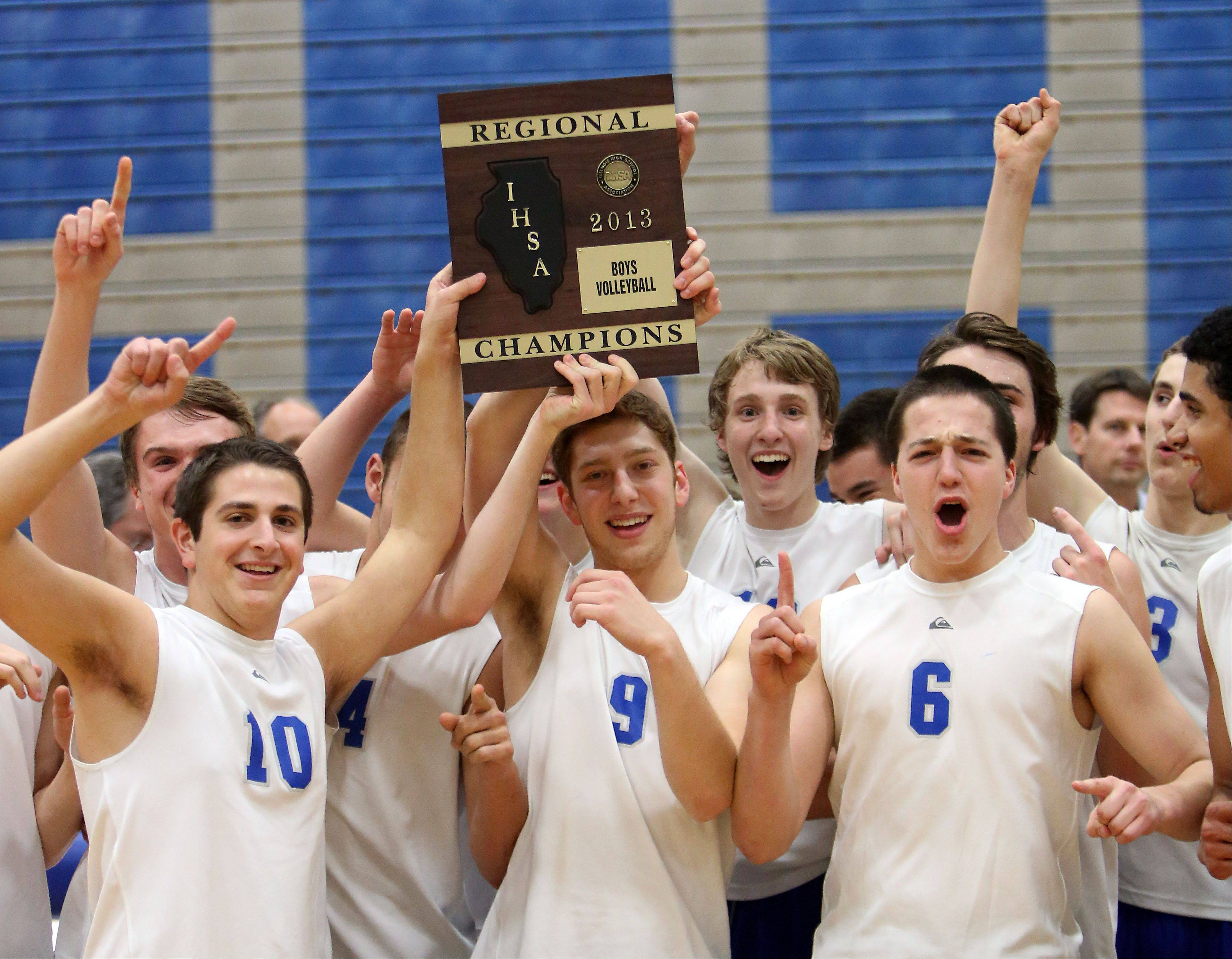 Vernon Hills boys volleyball players hoist the regional trophy after their win over Palatine on Wednesday night at Vernon Hills.
