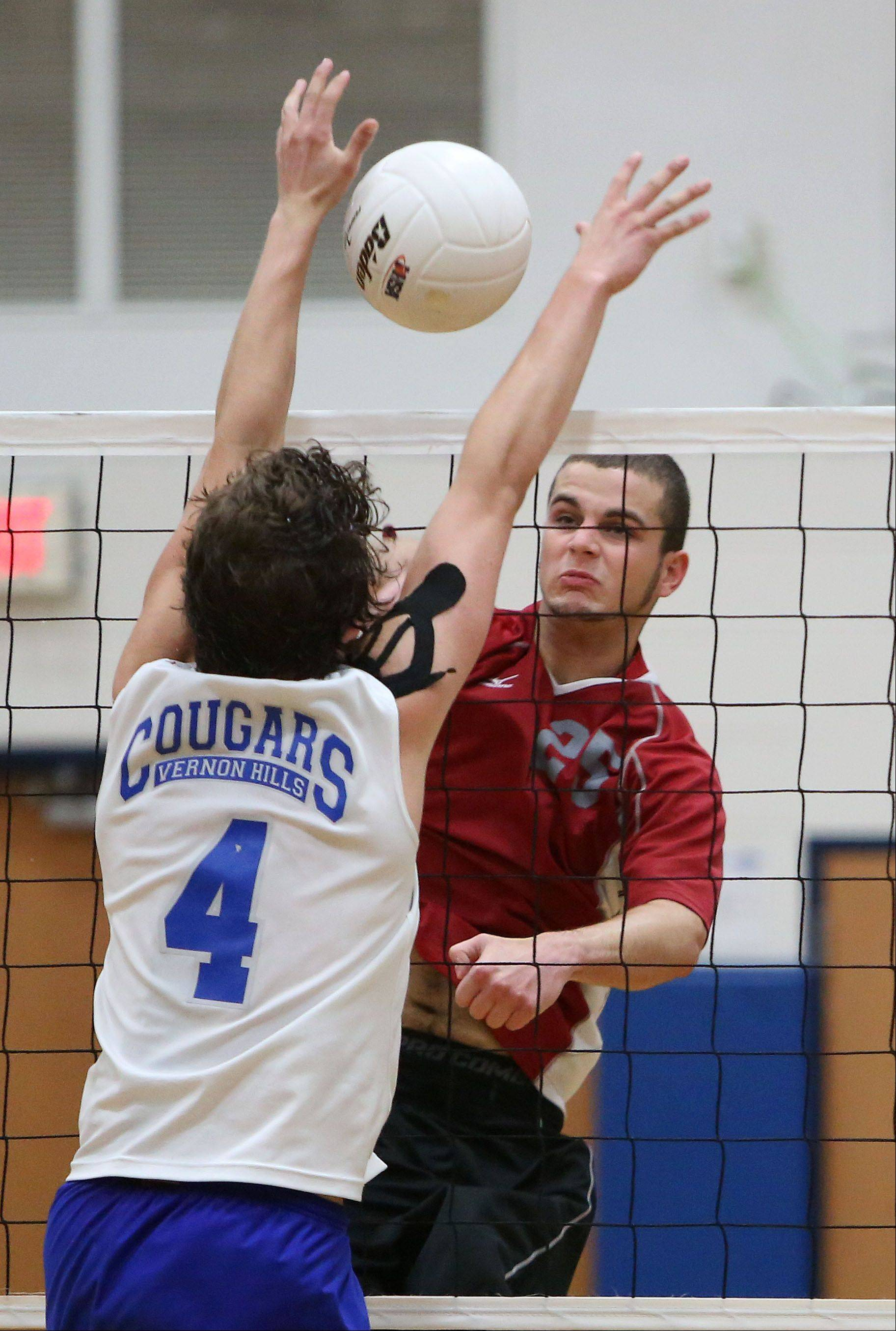 Vernon Hills' Tyler Small, left, and Palatine's Brian Keough meet at the net during regional volleyball action Wednesday night at Vernon.