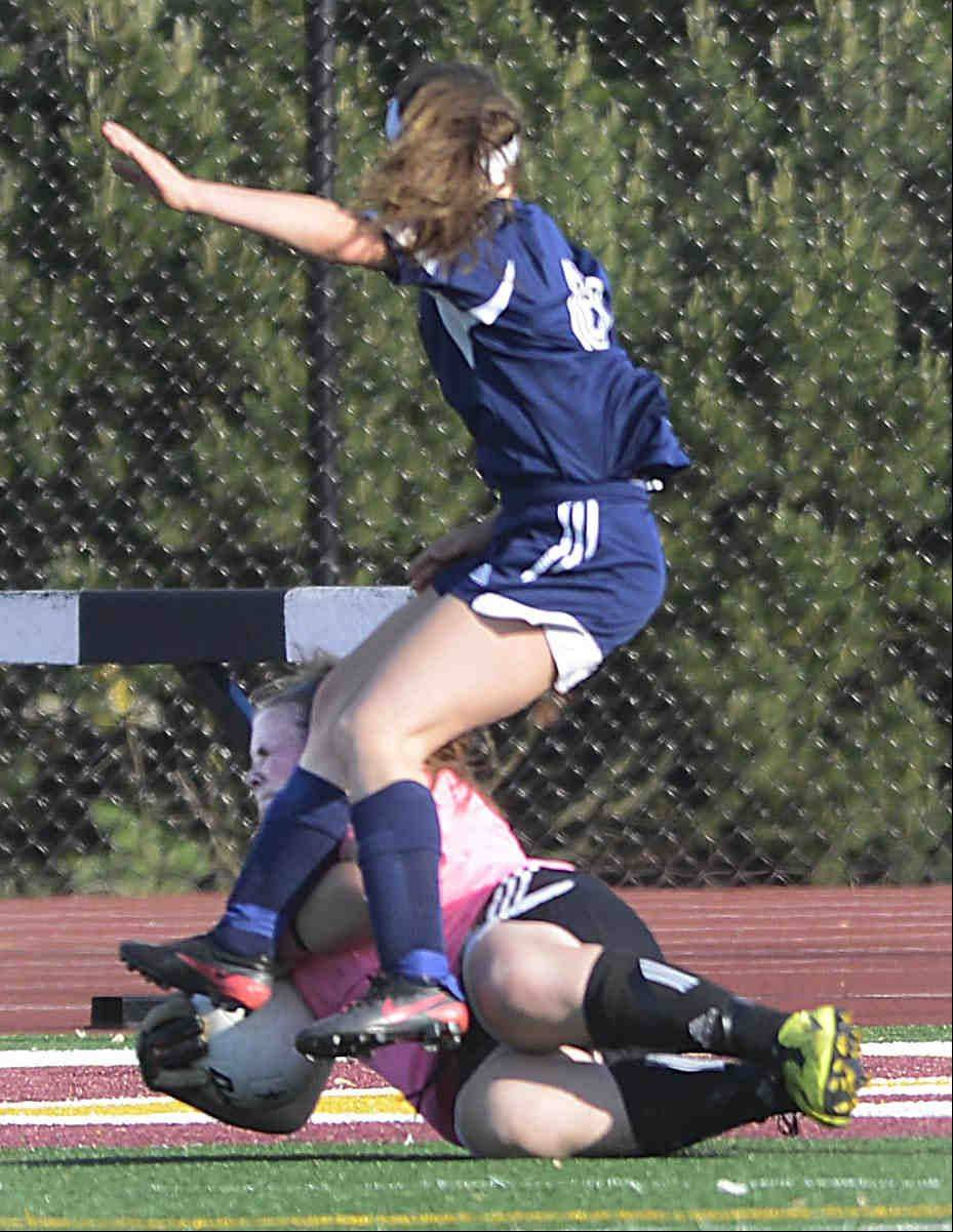 St. Edward goalkeeper Paige Dykstra slides under and takes out the legs of Francis W. Parker's Gaby Coetzee Tuesday in the supersectional playoff at Concordia University in River Forest.