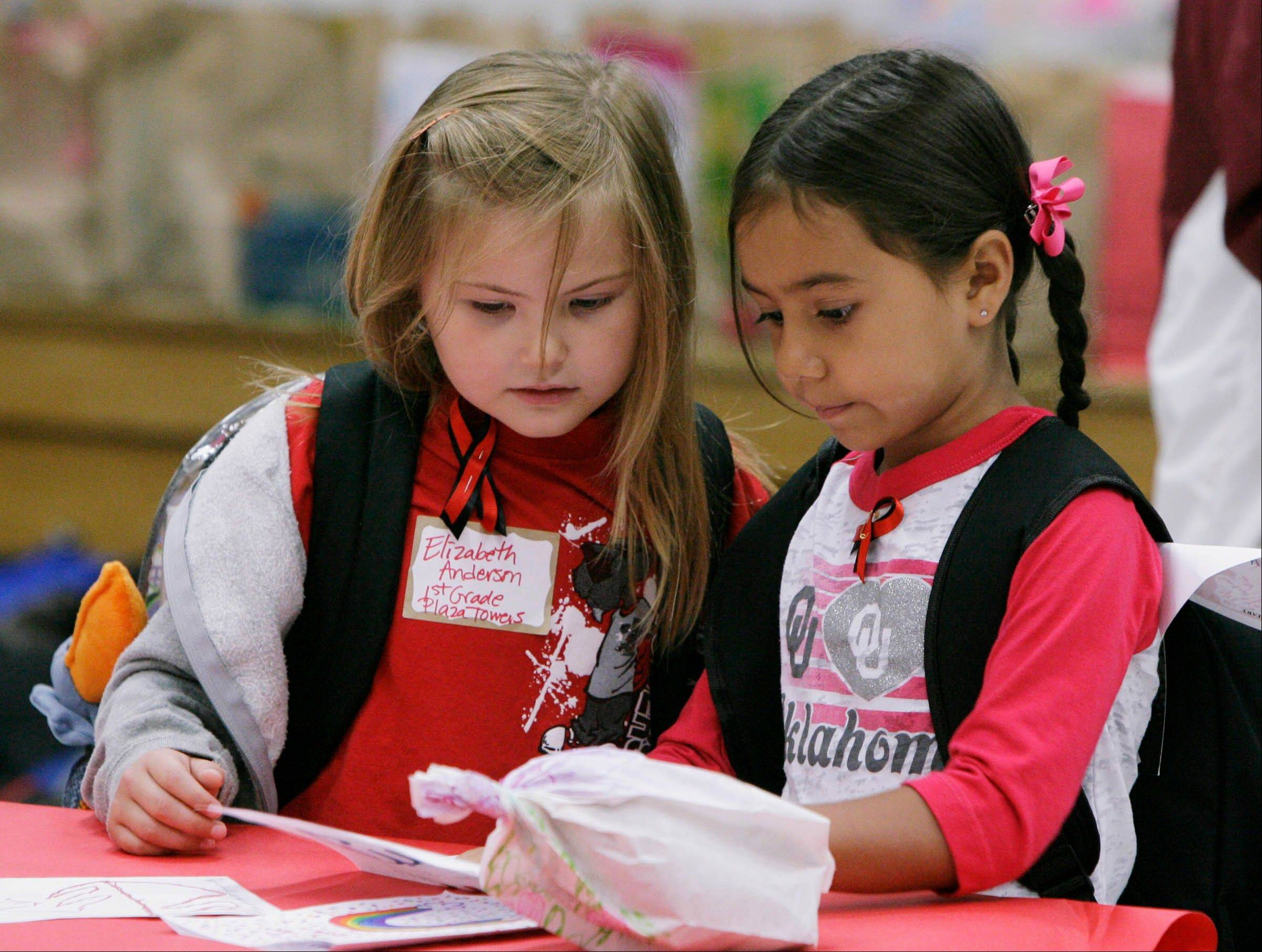 Classmates and survivors from Plaza Towers Elementary School Elizabeth Anderson, 6, left, and Rylee Pino, 6, read messages Wednesday from other children in the area during a visit to Eastlake Elementary School in Moore, Okla.