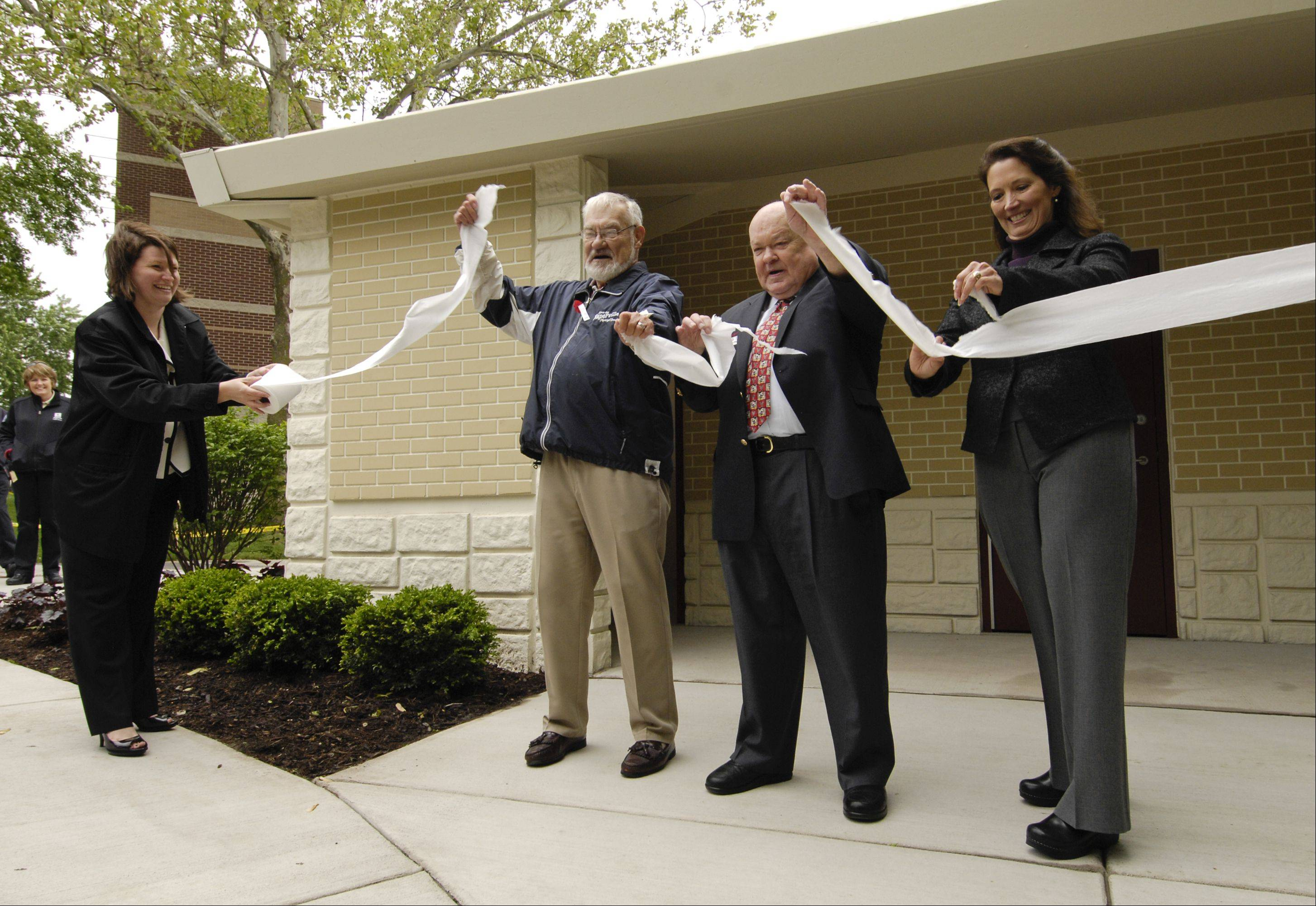 Naperville Municipal Band Director Ron Keller, Mayor George Pradel and park board President Kirsten Young tear a ribbon of toilet paper Thursday to open the new washroom facility at Central Park.