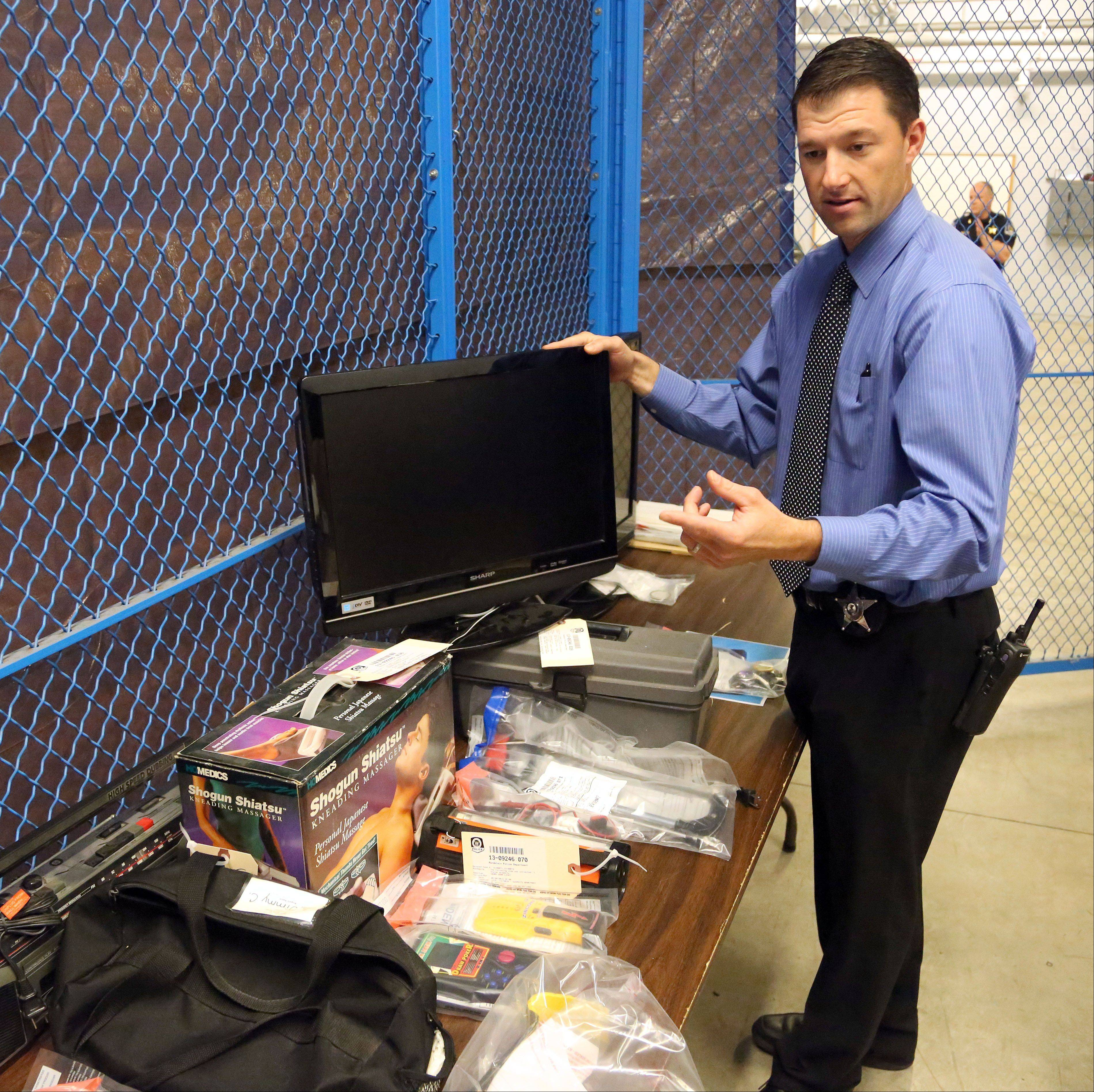 Mundelein Police Investigation Officer Jason Seeley reviews items recovered after two men were caught burglarizing a house in Mundelein. Police searched the suspects' homes and found the stolen items.