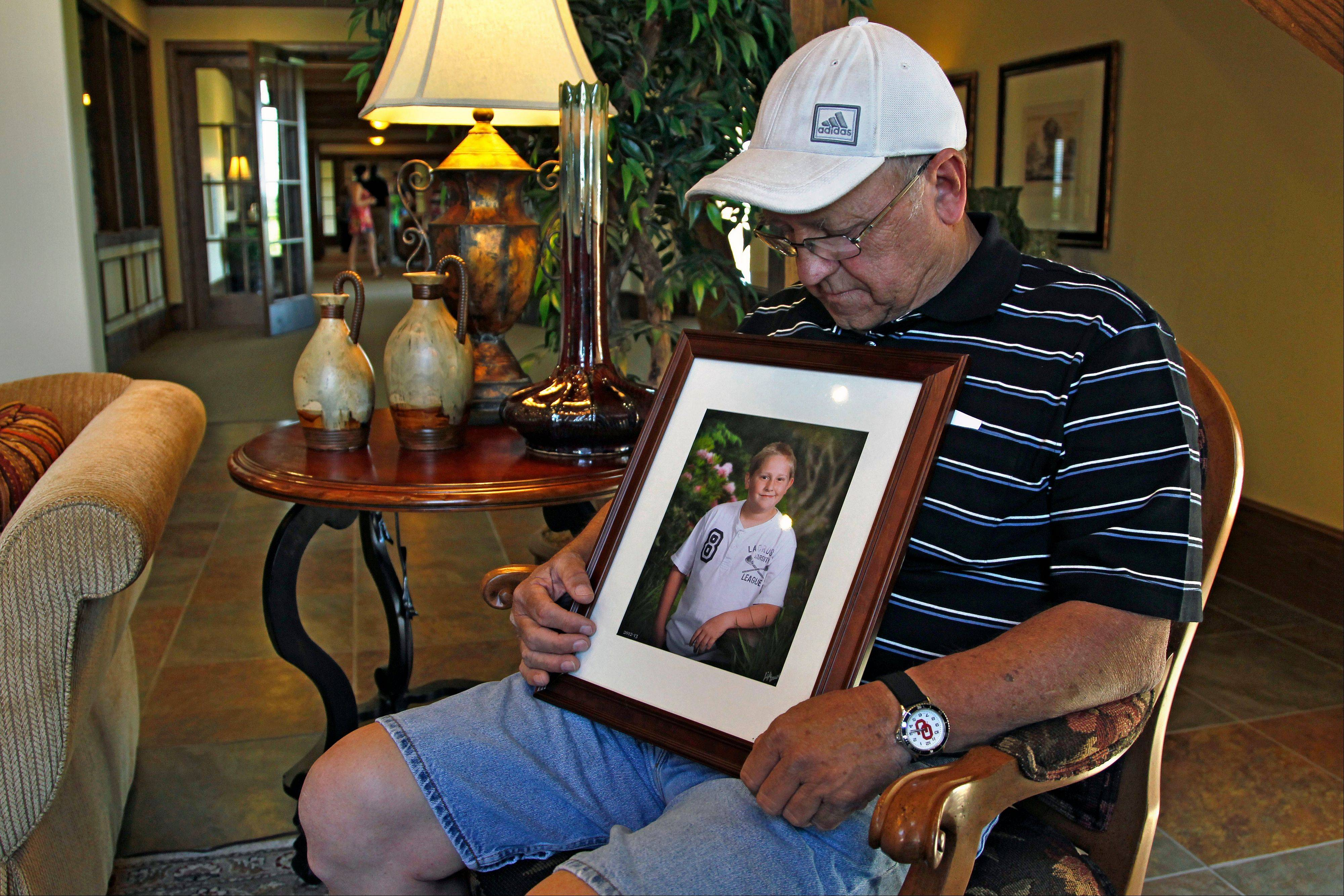 "Marvin Dixon, the grandfather of 8-year-old tornado victim Kyle Davis, glances down at a photo of his grandson in the lobby of a funeral home where his grandson awaits burial, in Oklahoma City, Wednesday, May 22, 2013. Nicknamed ""The Wall,"" Davis loved soccer and going to the Monster Truck exhibitions at the fairgrounds with his grandfather."