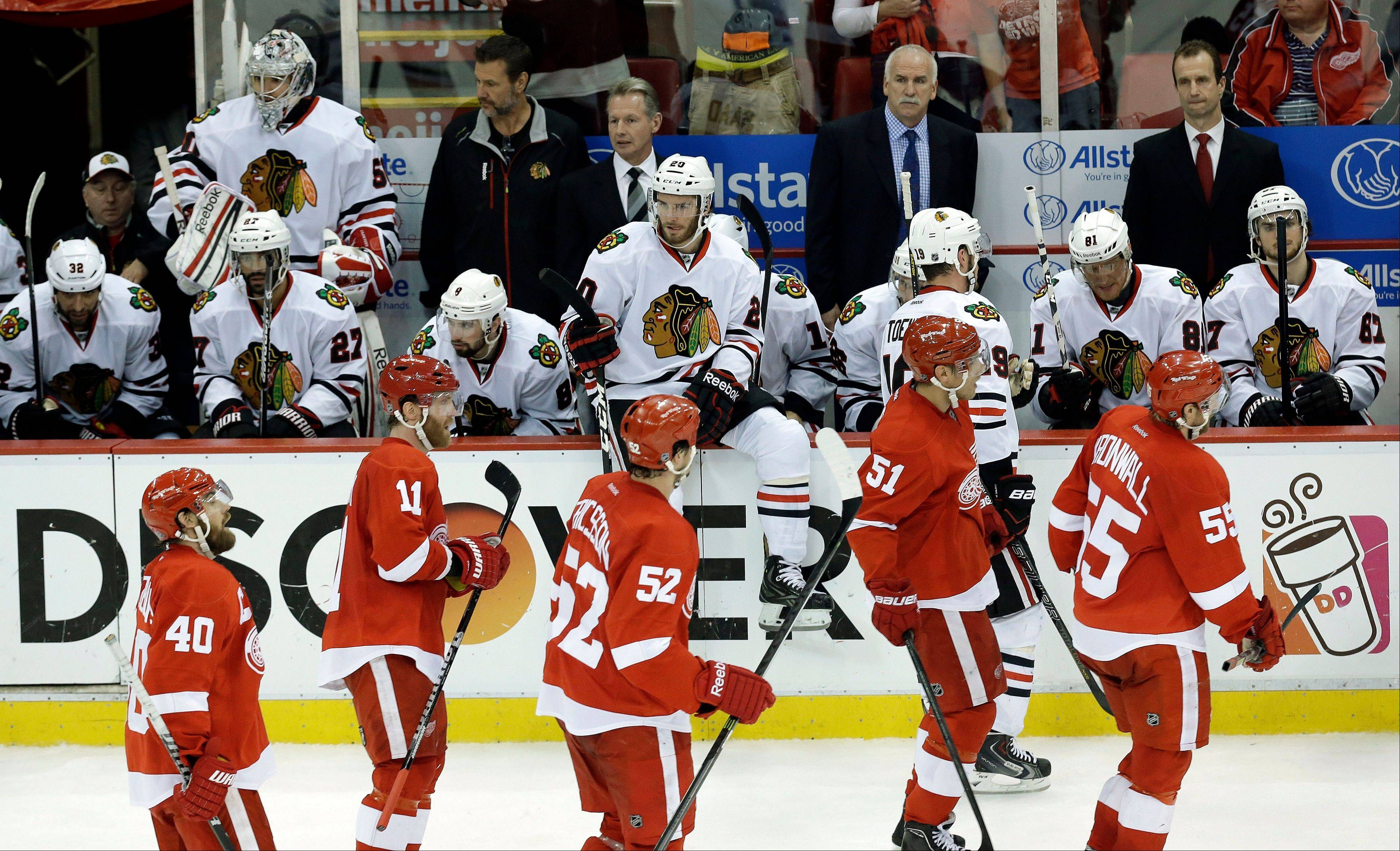 Detroit Red Wings, foreground, skate past the Chicago Blackhawks bench after Daniel Cleary�s empty-net goal during the third period.