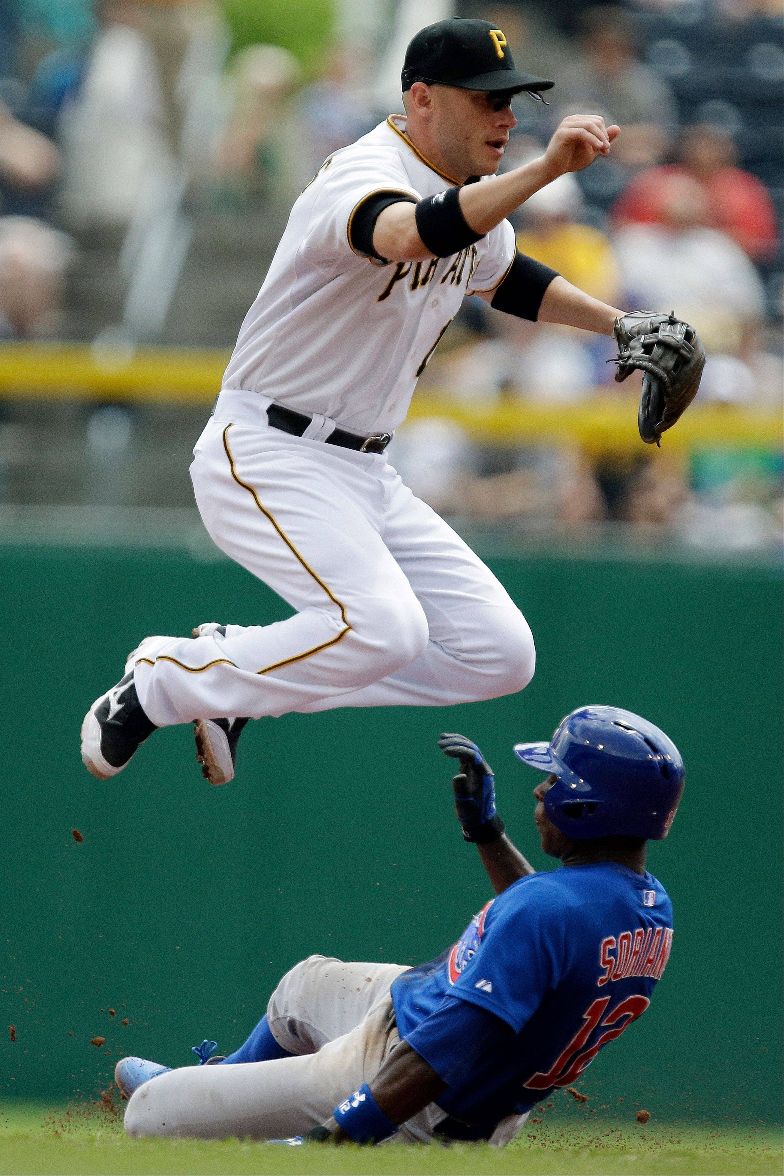 Pittsburgh Pirates shortstop Clint Barmes (12) leaps to avoid Chicago Cubs' Alfonso Soriano (12) at second base while turning a double play on the Cubs' Nate Schlerholtz at first base during the second inning of a baseball game in Pittsburgh, Thursday, May 23, 2013. (AP Photo/Gene J. Puskar)