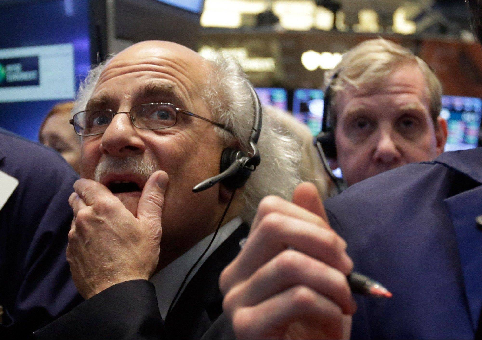 Trader Peter Tuchman, left, works Thursday on the floor of the New York Stock Exchange.