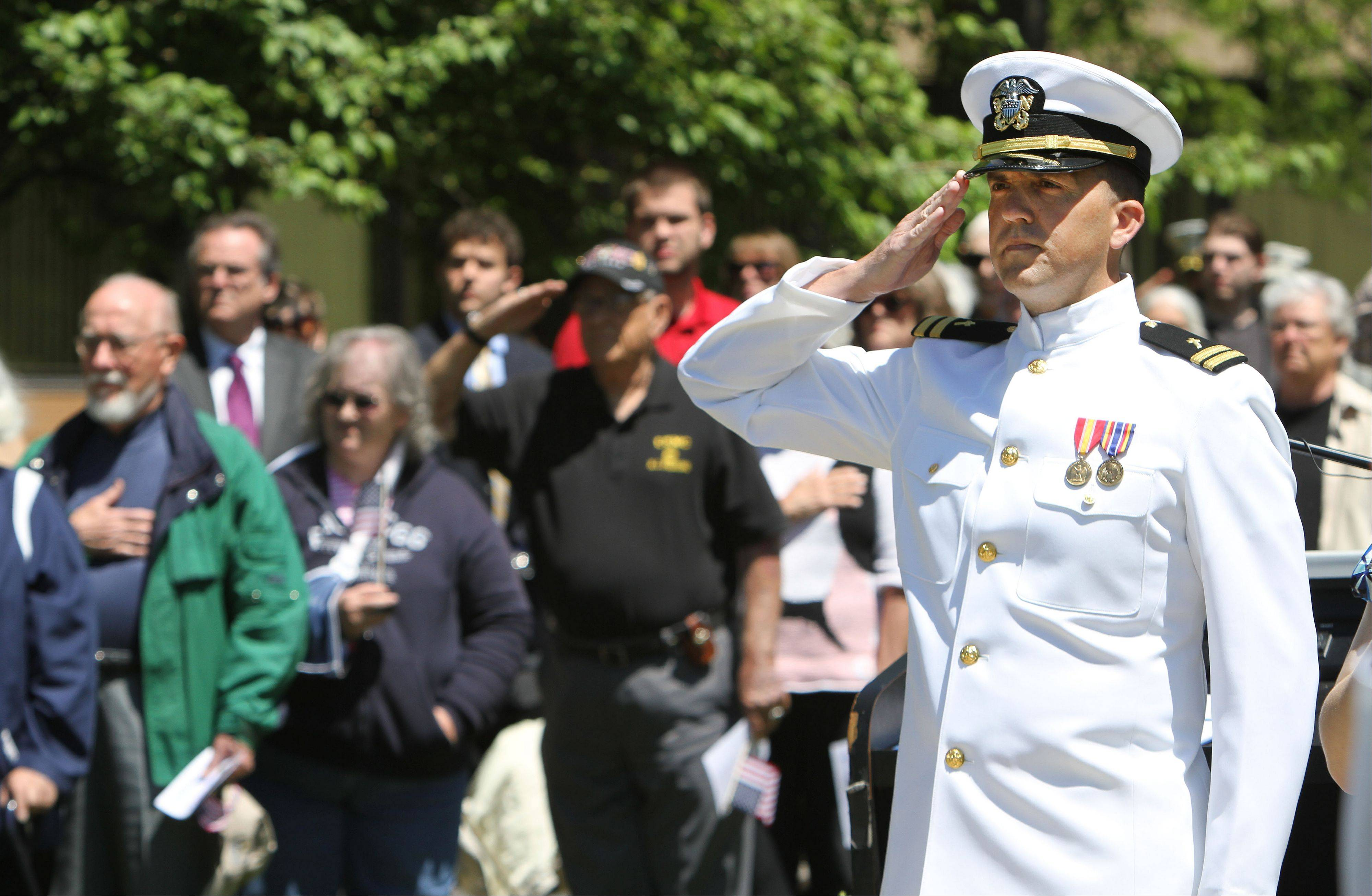 Navy Lt. William Butt salutes during the national anthem Friday at the sixth annual Memorial Day ceremony at the College of Lake County in Grayslake.