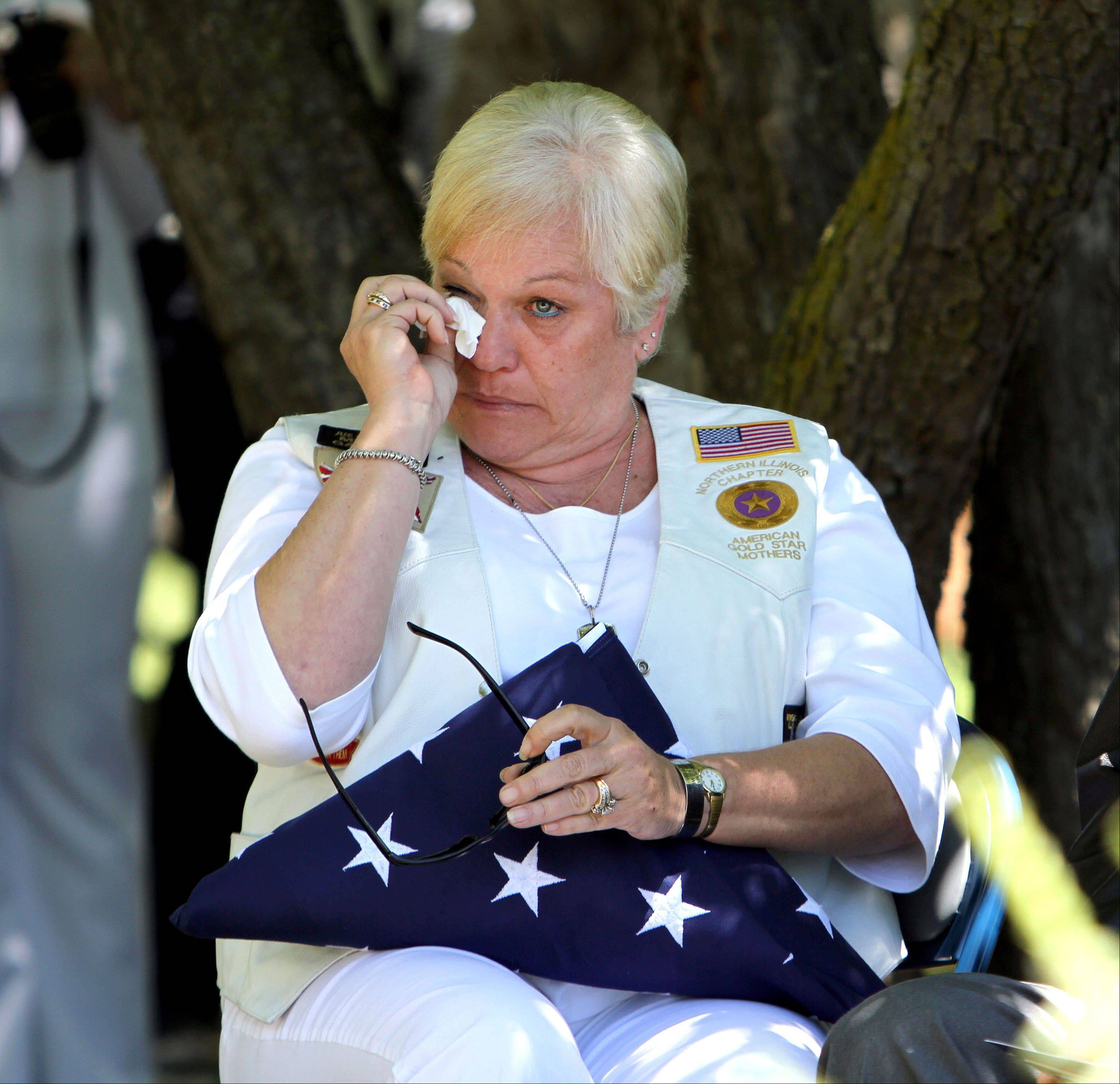 Janet Maher of Grayslake wipes tears from her eyes after being presented an American flag during the ceremony. Maher is the mother of Lance Cpl. Sean Maher, a Marine killed in Iraq in 2005.