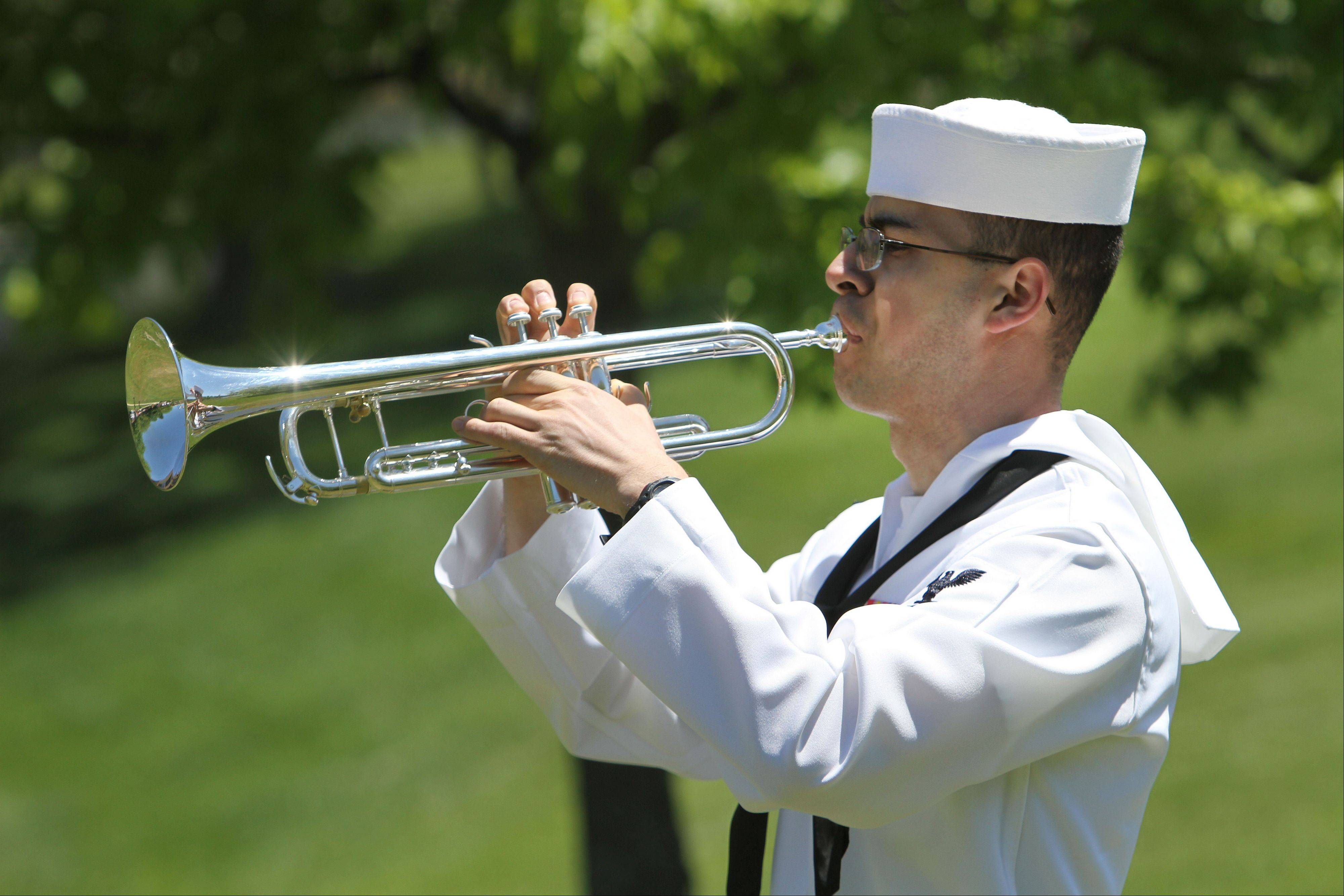 Navy Petty Officer Third Class Del Ross plays taps during the Memorial Day ceremony at the College of Lake County in Grayslake on Friday.