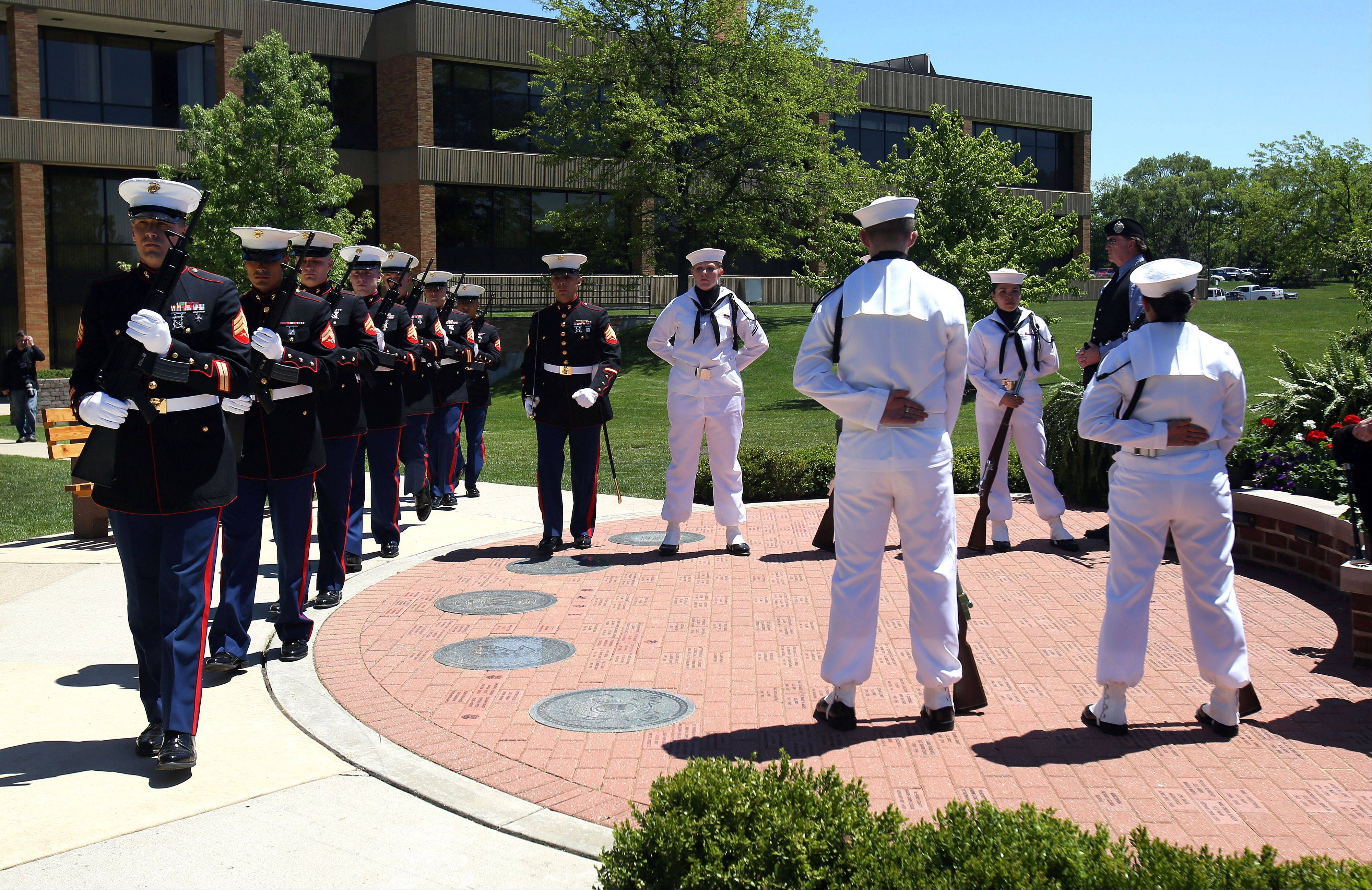 A Marine Corps firing detail, left, and the Navy Training Support Center Drill Team perform during the sixth annual Memorial Day ceremony at the College of Lake County Friday.