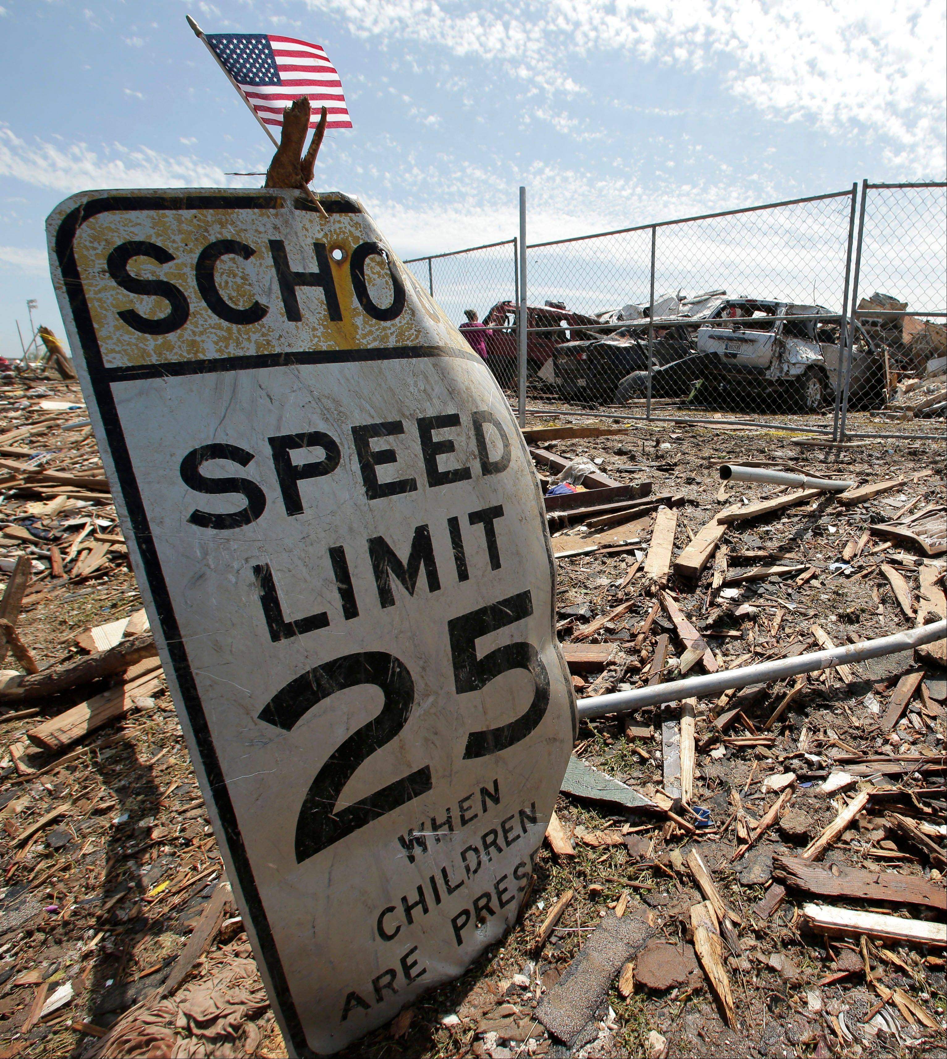 A battered sign stands Thursday outside the wreckage of Plaza Towers Elementary School, where seven children were killed earlier in the week when a tornado hit Moore, Okla.