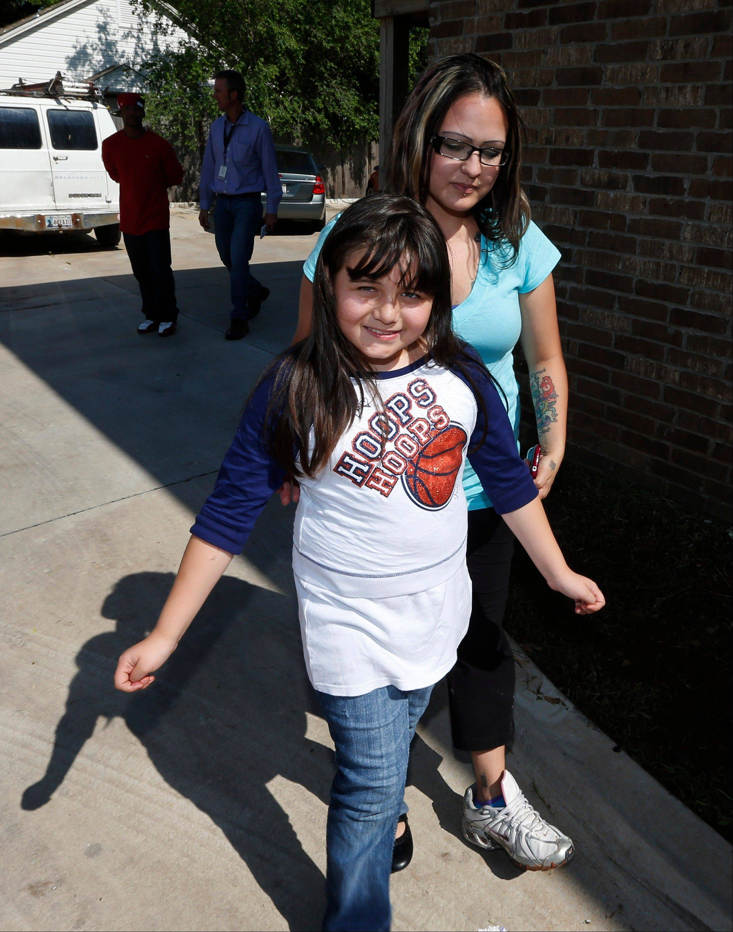Jazmin Rodriguez, left, smiles as she walks with her mother, LaTisha Garcia, right, following an interview in Moore, Okla., Thursday.