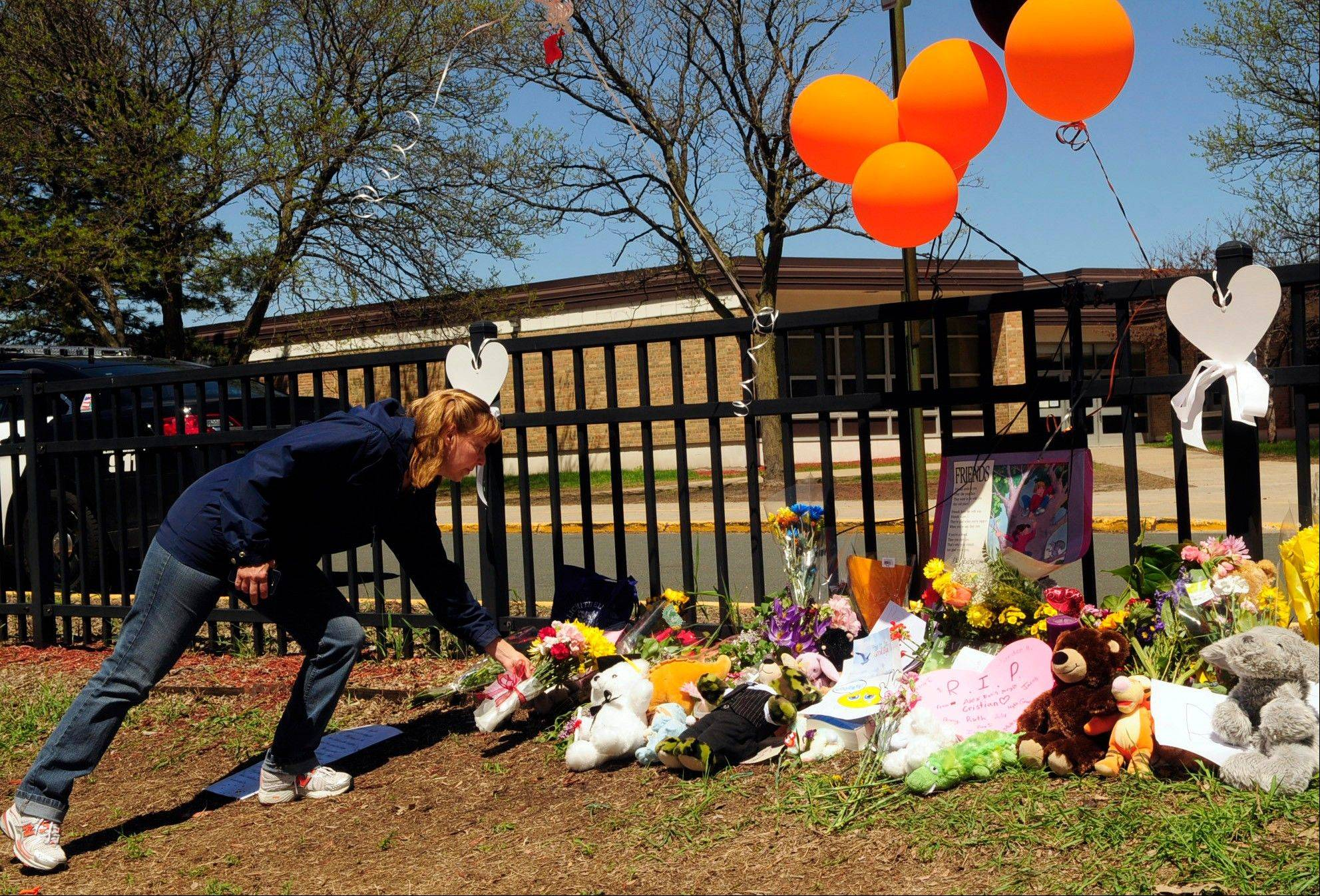 Laurie Amos of St. Louis Park, places flowers Thursday by a makeshift memorial in front of Peter Hobart Elementary School in St. Louis Park, Minn.