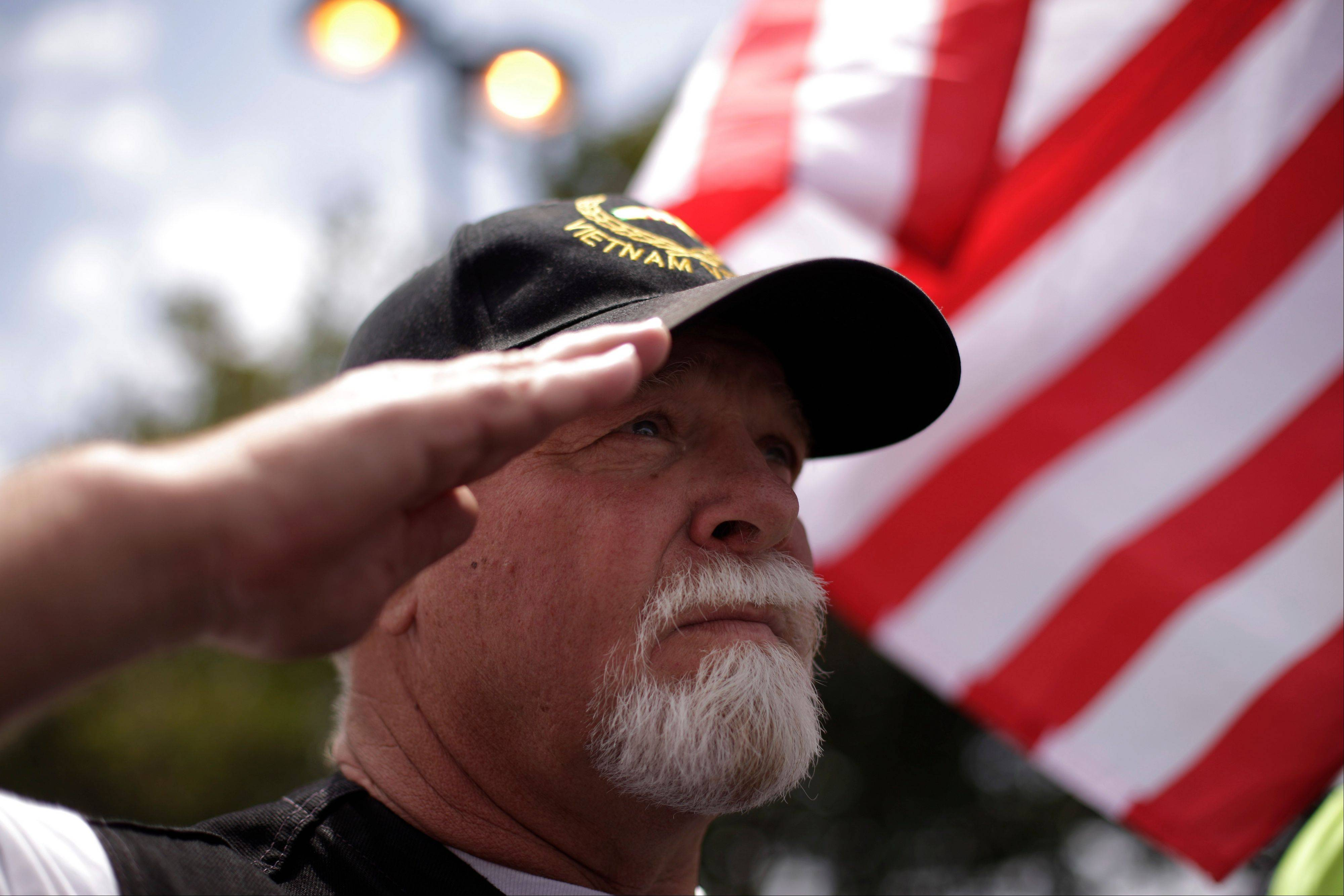 Vietnam War veteran Tedd Hybbert salutes Thursday as he watches some 200 Vietnam POWs arrive to celebrate their 40th reunion at the Richard Nixon Presidential Library & Museum in Yorba Linda, Calif.