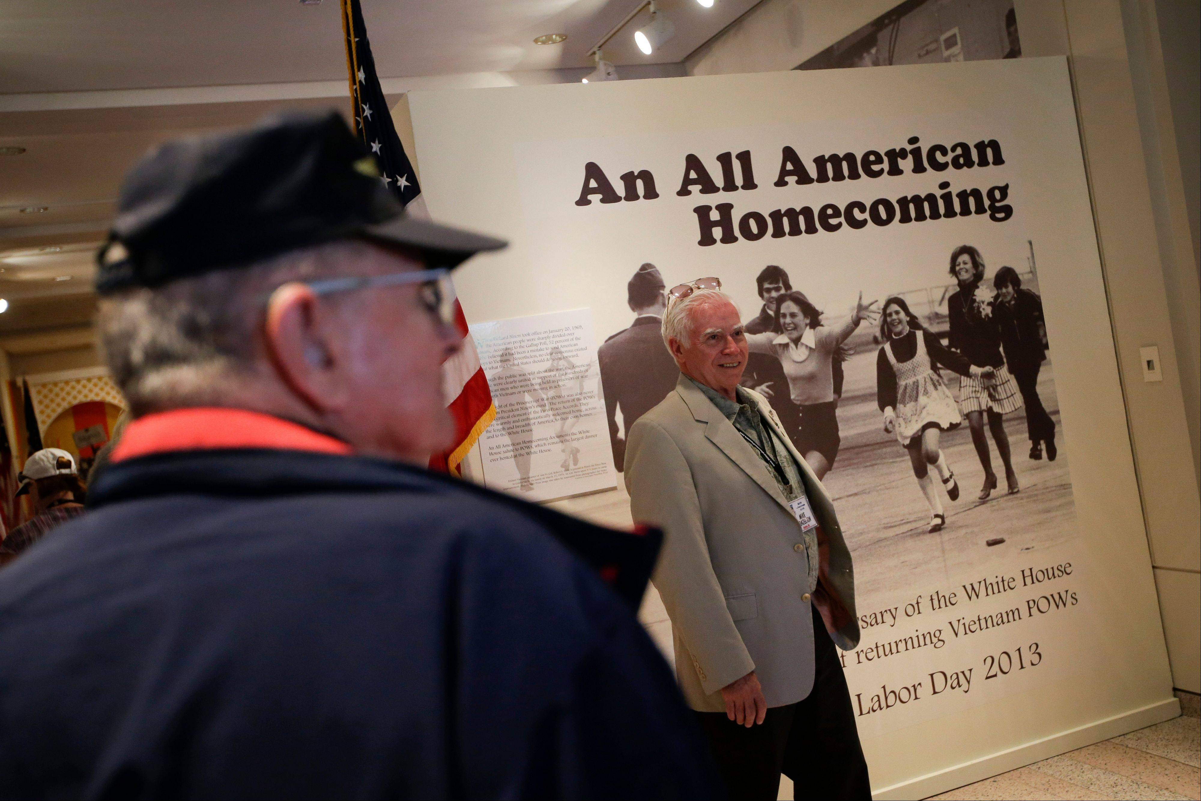 Former Vietnam POW Mike Brazelton, center, poses in front of a Pulitzer prize winning photo showing released prisoner of war Lt. Col. Robert L. Stirm being greeted by his family at Travis Air Force Base in Fairfield, Calif.