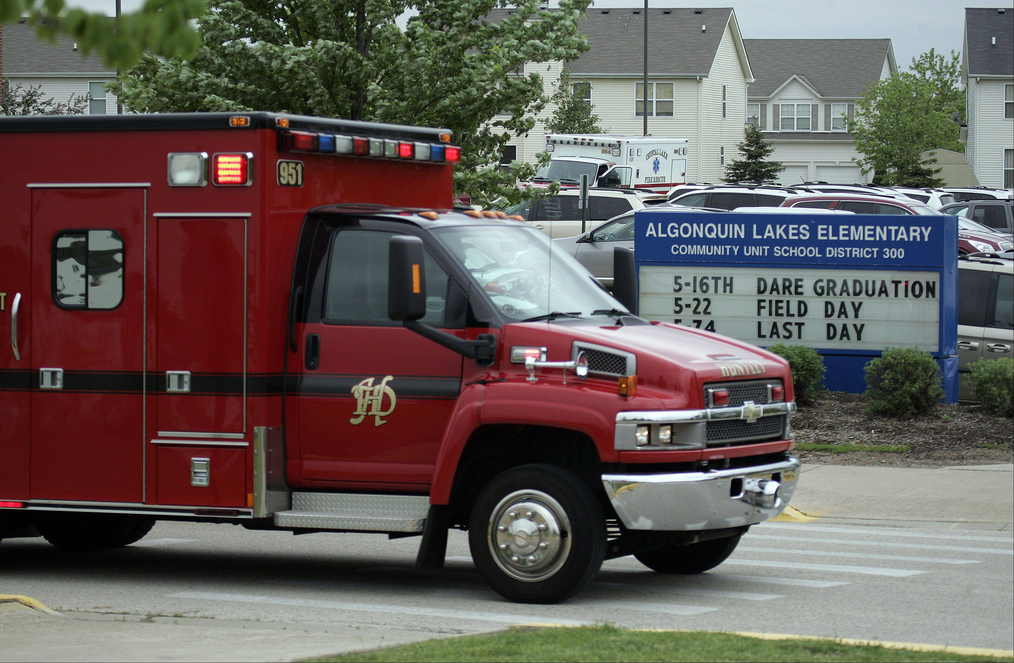 An ambulance leaves Algonquin Lakes Elementary School after six students were sent to two hospitals following an accident that involved a bounce house and possibly an inflatable slide.