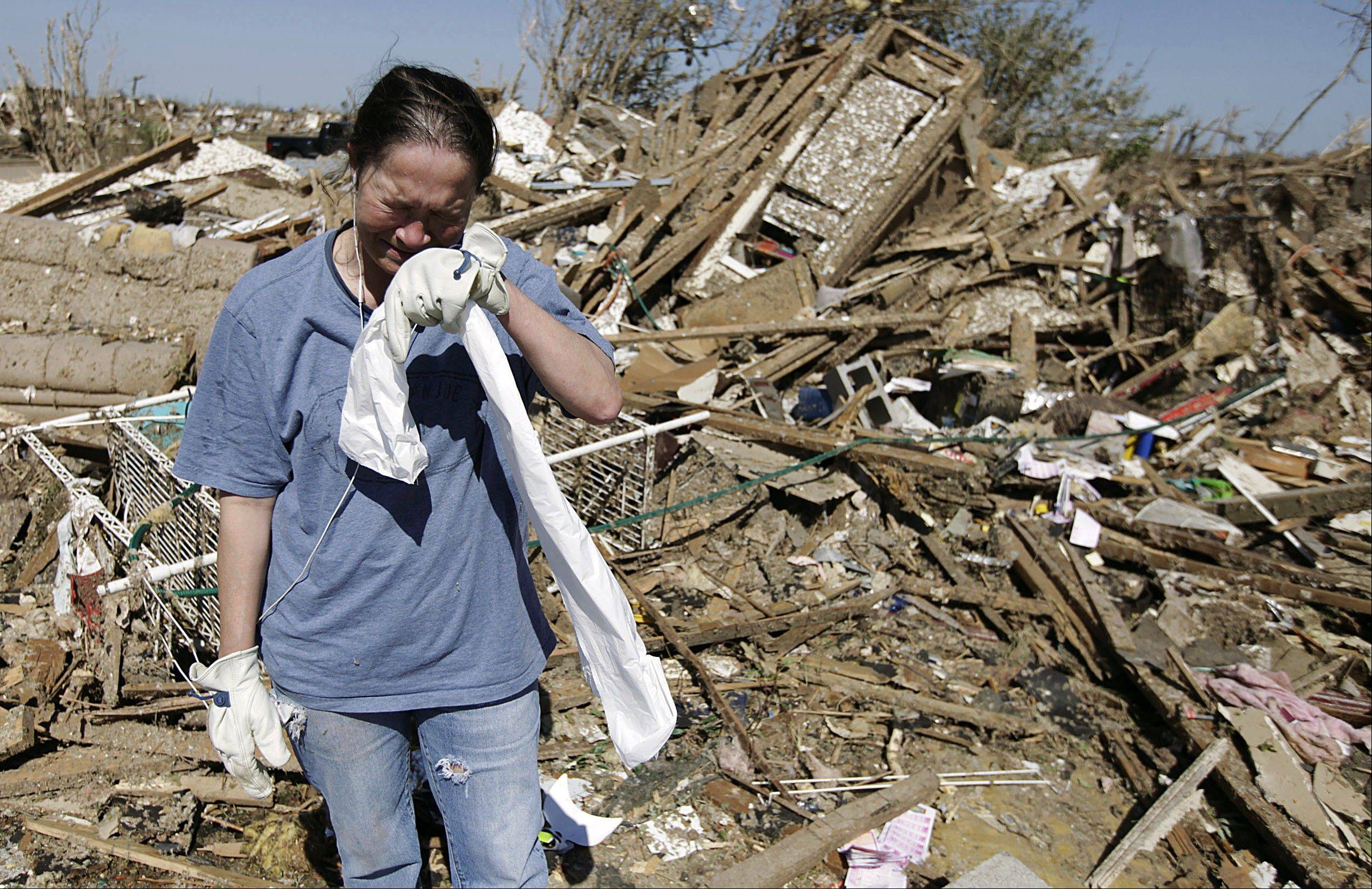 Kriket Krekemeyer cries while cleaning up her tornado-ravaged home in Moore, Okla., Wednesday, May 22, 2013.