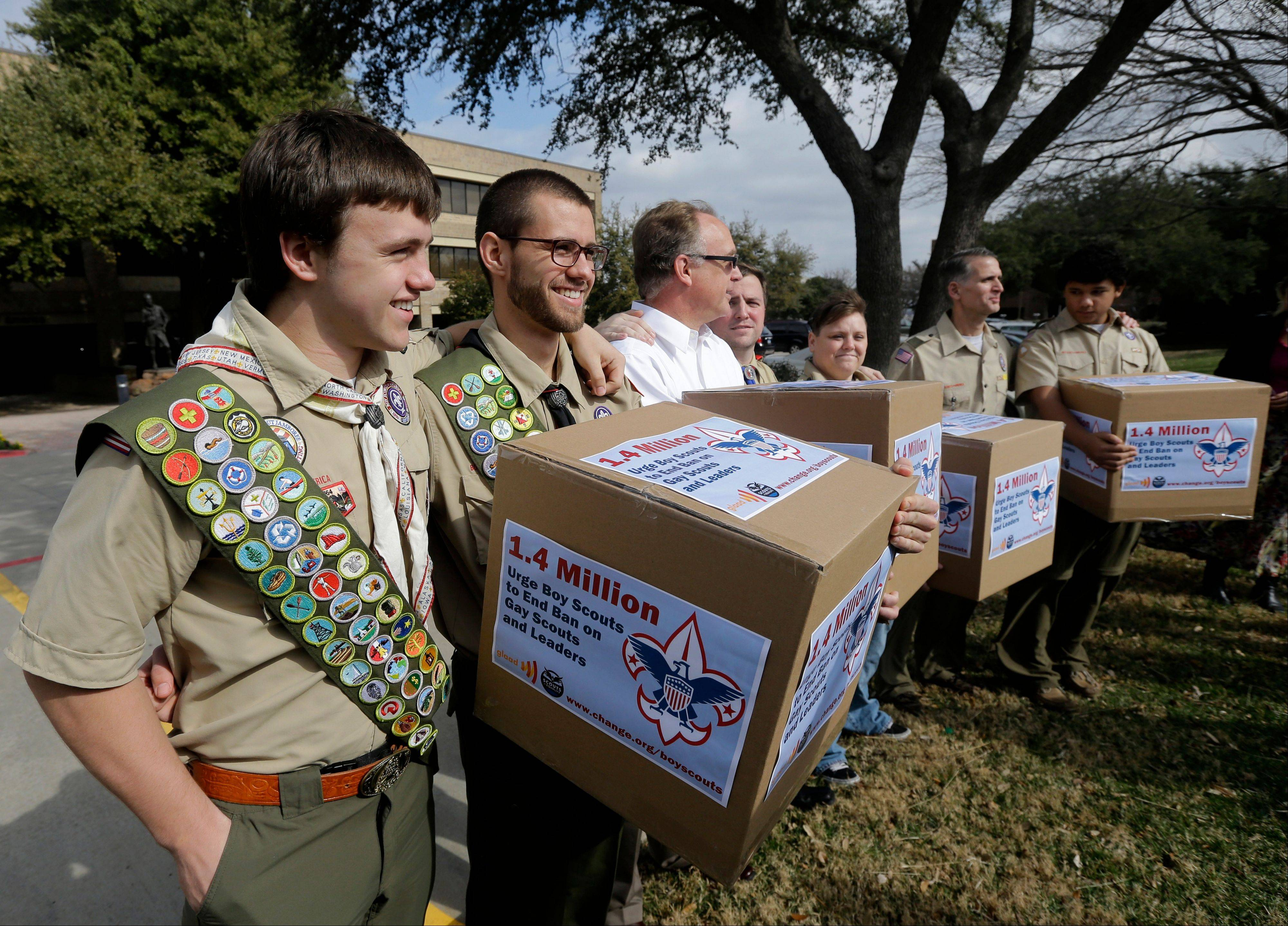 James Oliver, left, hugs his brother and fellow Eagle Scout, Will Oliver, who is gay, as Will and other supporters carry four boxes filled with petitions to end the ban on gay Scouts and leaders.