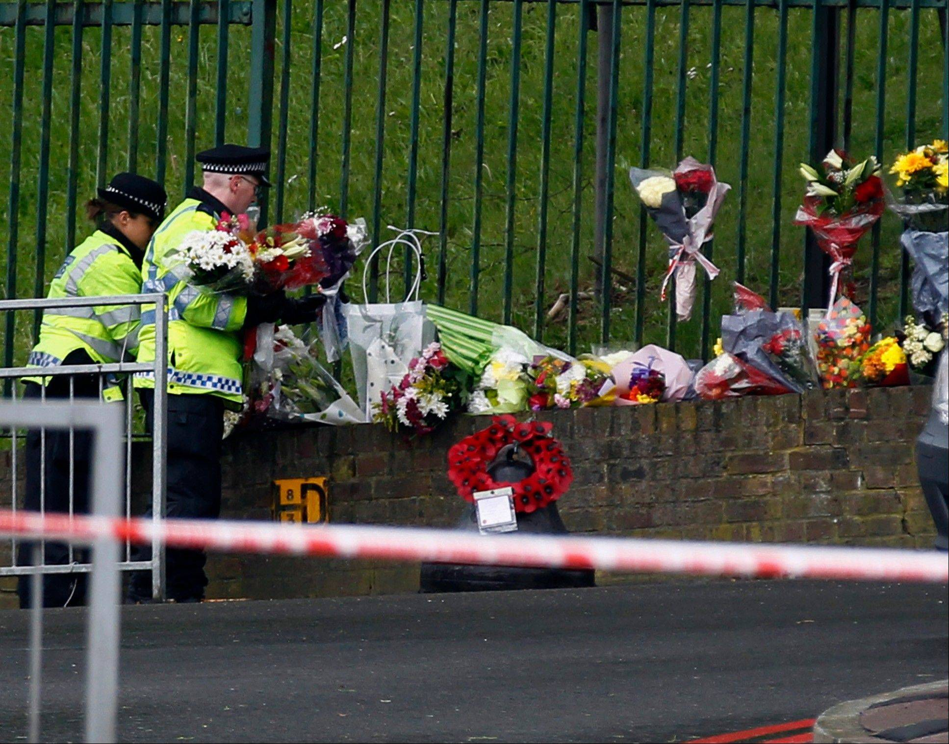 Police officers lay down floral tributes handed to them by members of the public at the scene of a terror attack in Woolwich, southeast London, Thursday, May 23, 2013. The British government's emergency committee met Thursday after two attackers killed a man in a daylight attack in London that raised fears terrorism had returned to the capital.