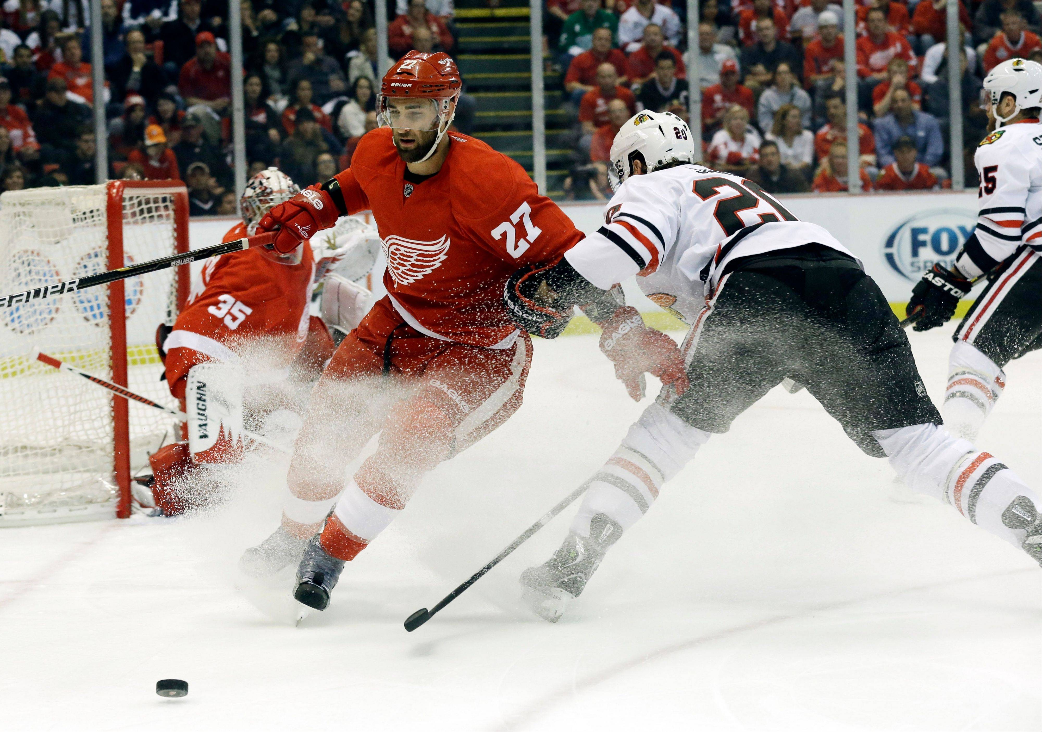 Detroit Red Wings defenseman Kyle Quincey (27) and Chicago Blackhawks left wing Brandon Saad (20) battle for the puck during the first period.