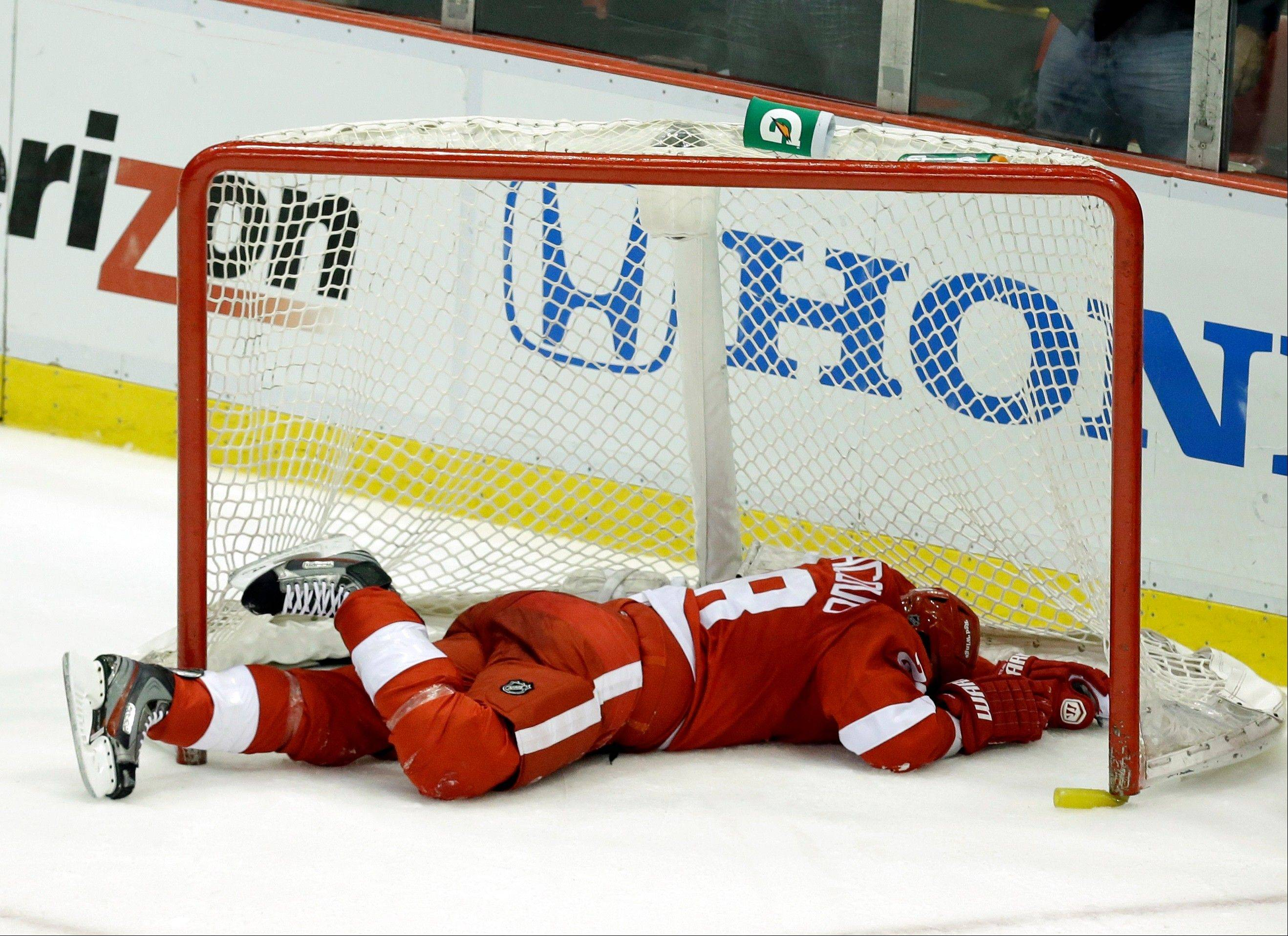 Detroit Red Wings defenseman Carlo Colaiacovo lies in the net after coming off its posts against the Chicago Blackhawks during the third period.