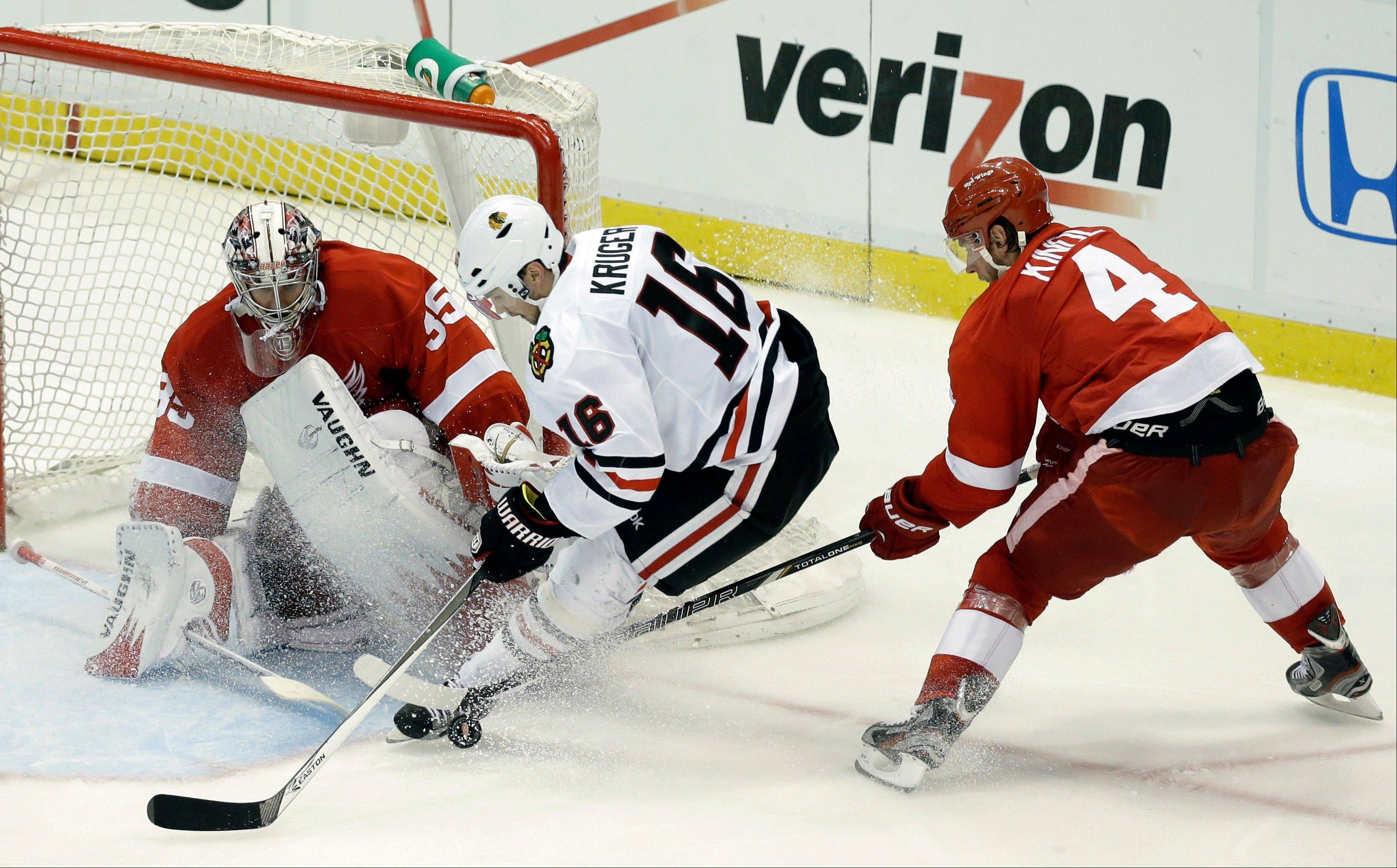 Detroit Red Wings defenseman Jakub Kindl (4), of the Czech Republic, defends against Chicago Blackhawks center Marcus Kruger (16), of Sweden, in front of Detroit Red Wings goalie Jimmy Howard (35) during the third period.