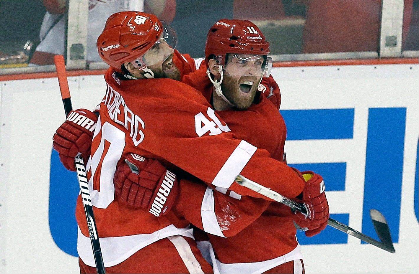 Detroit Red Wings right wing Daniel Cleary, right, celebrates his empty-net goal against the Chicago Blackhawks with teammate Henrik Zetterberg (40), of Sweden, during the third period.