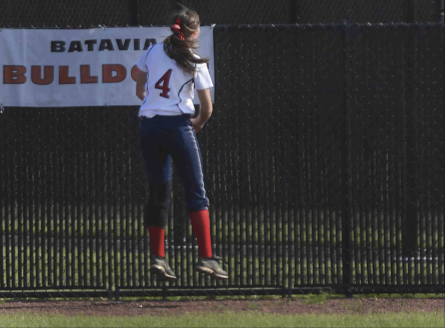 South Elgin outfielder Brittany Koss bounces as she runs out of room and watches a home run ball by Elgin's Monica Stockman bounce outside the fence in the regional semifinal game at St. Charles North Thursday. The home run brought the Maroons within one at 3-2.