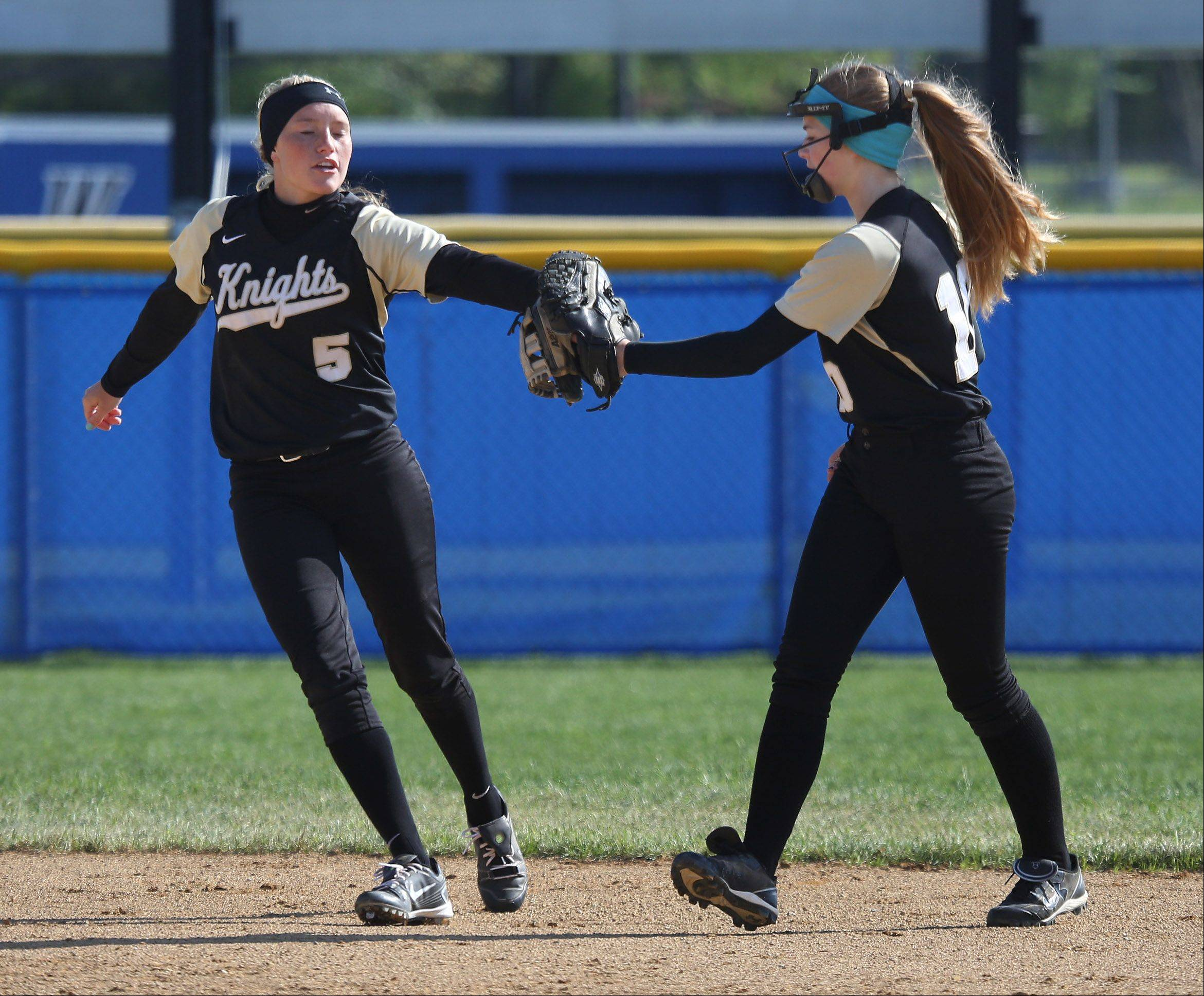 Grayslake North shortstop Jordyn Bowen, left, touches gloves with teammate Kayla Switalla after getting an out during Class 4A regional semifinal play Thursday at Warren.