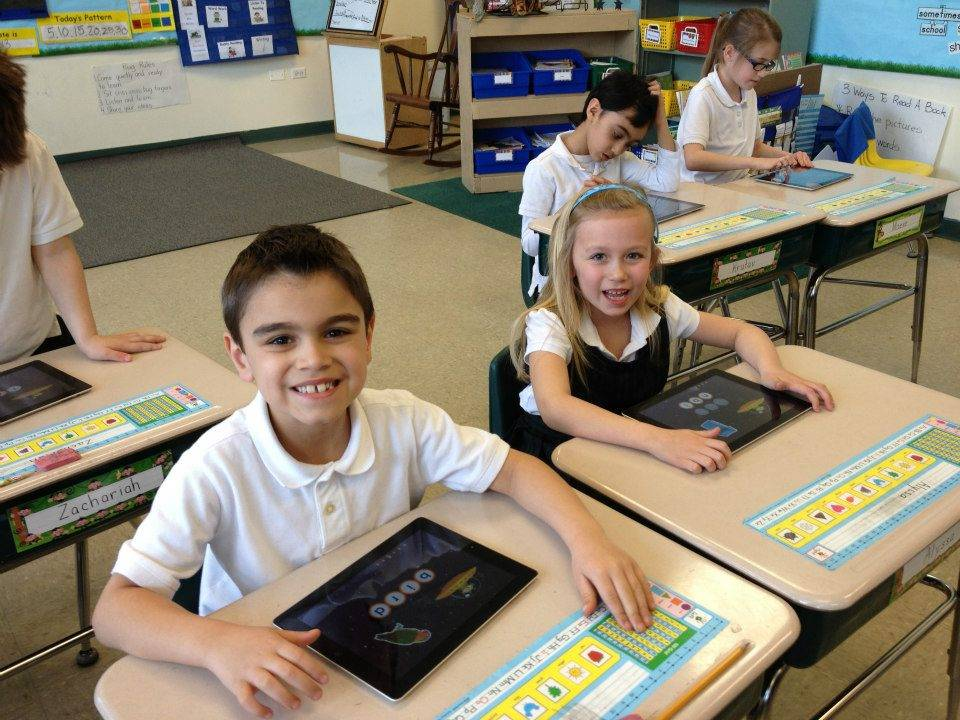 Saint Alphonsus Liguori First Graders Kaiden Ghazvini and Alyssa Haisman use iPads to enhance their reading.