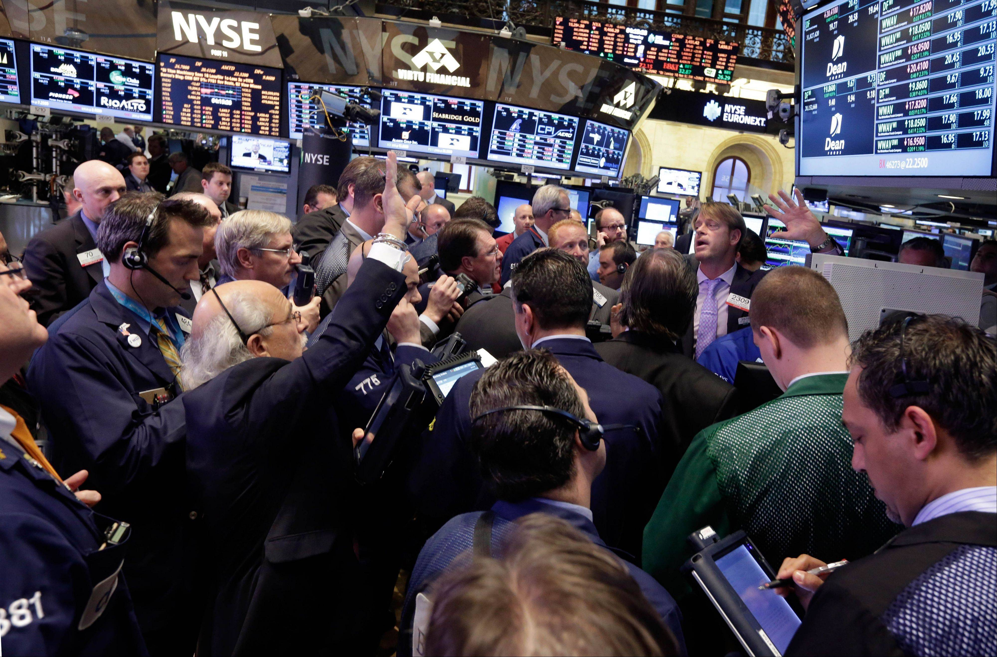 Traders gather at a post on the floor of the New York Stock Exchange Thursday at the close of trading.